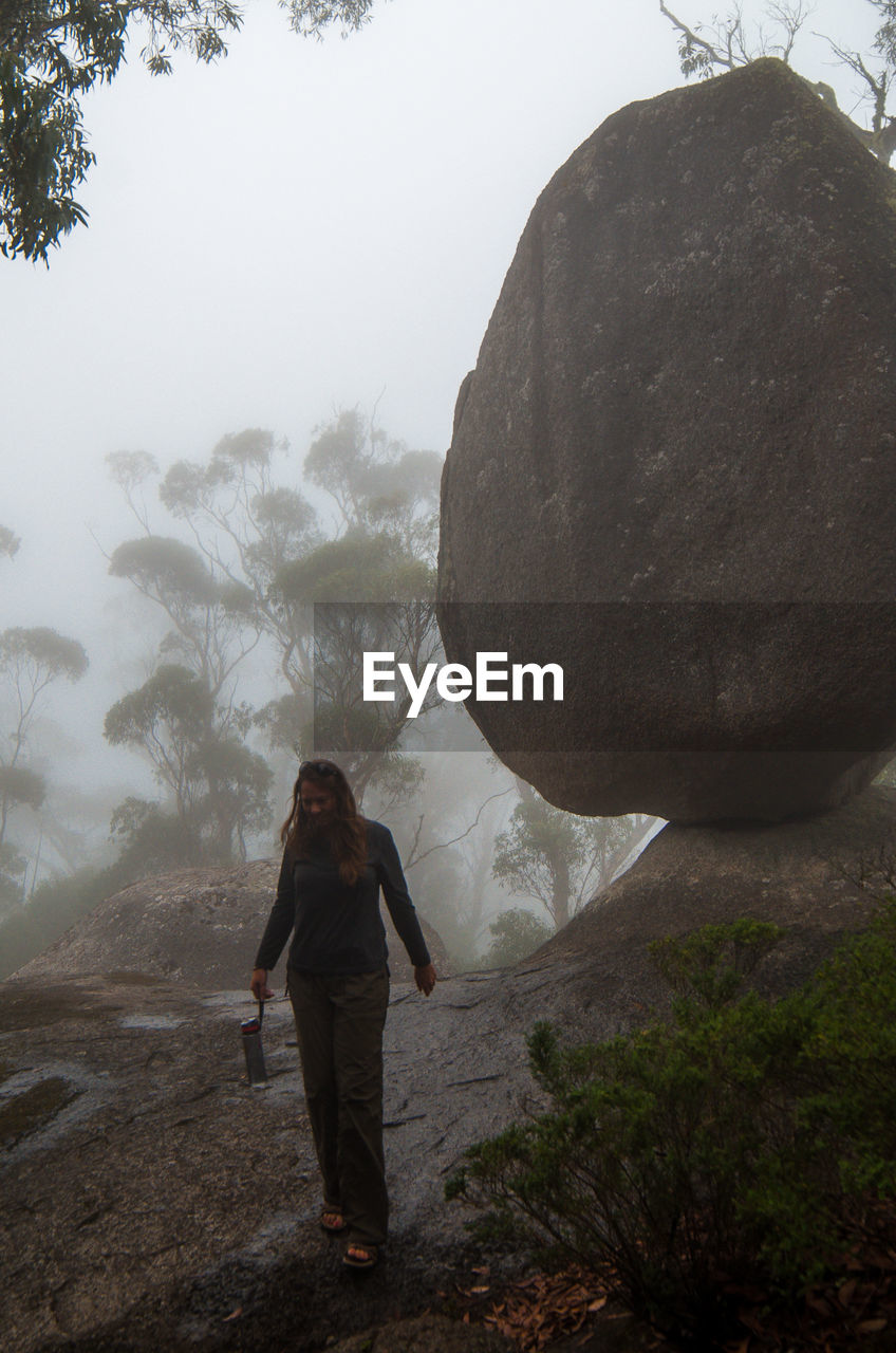 rock - object, real people, mountain, rear view, fog, nature, rock formation, one person, full length, landscape, beauty in nature, adventure, outdoors, day, standing, leisure activity, tree, hiking, lifestyles, climbing, women, scenics, cliff, waterfall, sky, power in nature, young adult, adult, people