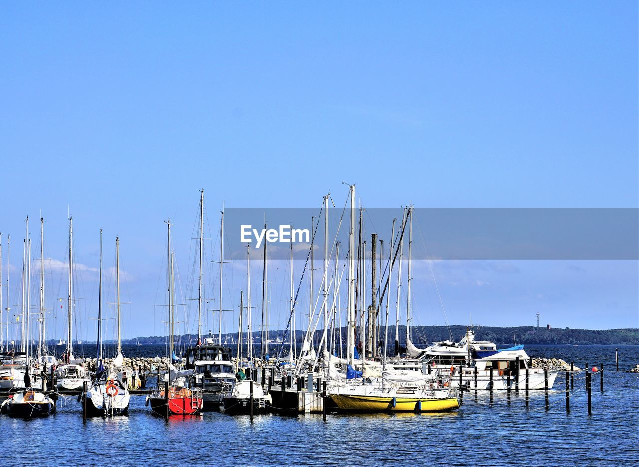 nautical vessel, transportation, water, mode of transportation, sailboat, sky, mast, moored, pole, harbor, waterfront, clear sky, nature, sea, no people, day, copy space, blue, beauty in nature, outdoors, yacht, port, marina, wooden post