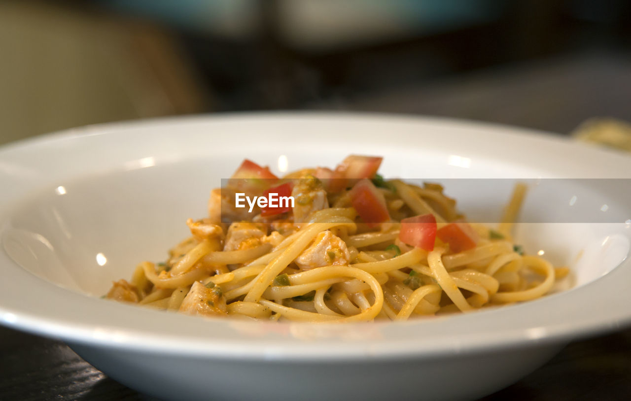 Close-up of spaghetti served in bowl on table