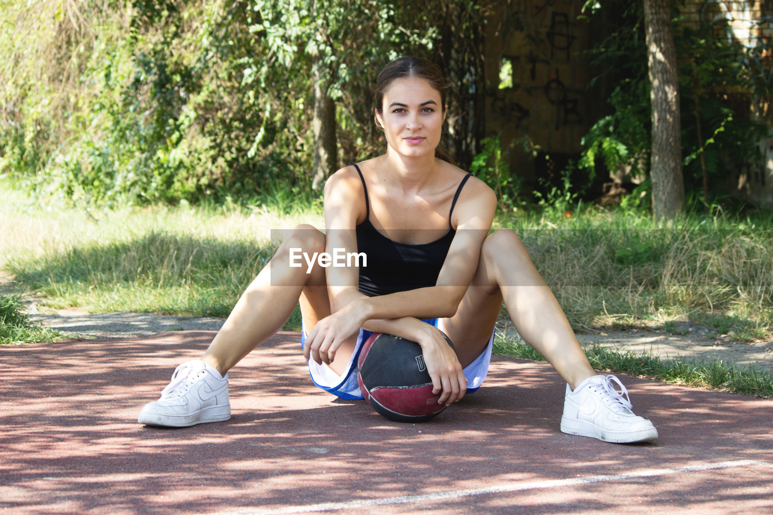 Portrait of basketball player with ball sitting on field