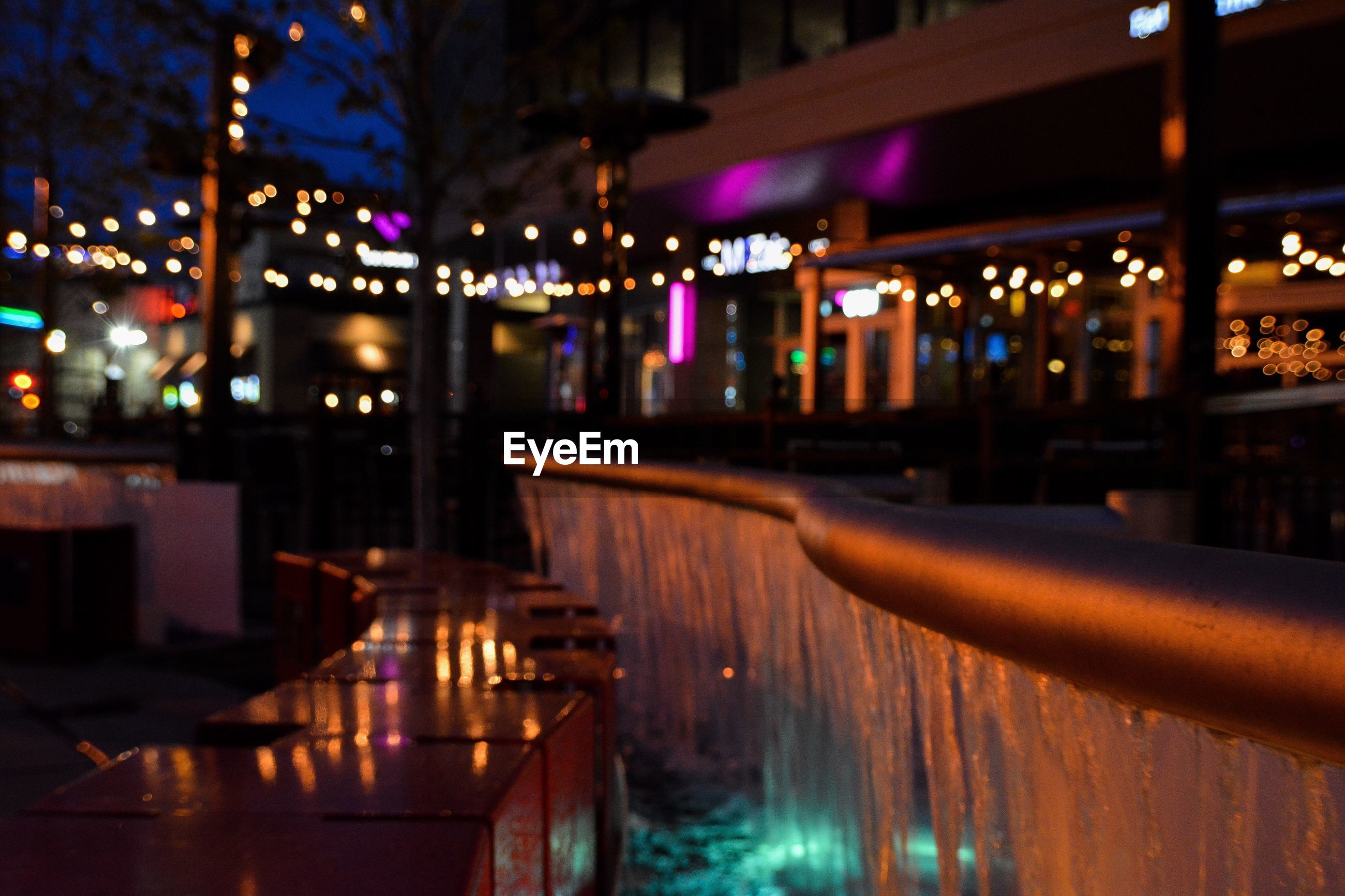 Fountain by bench against illuminated buildings