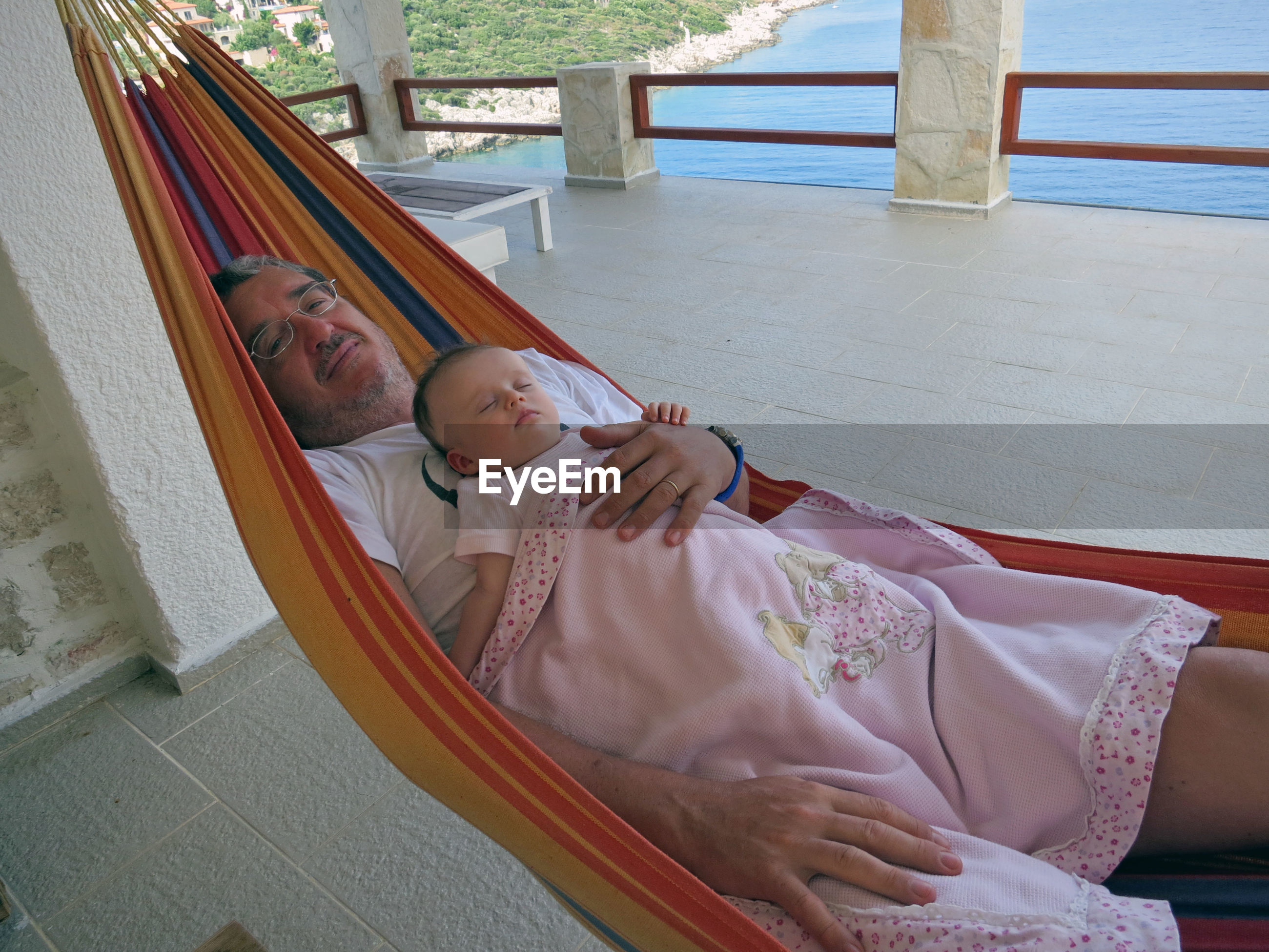 Portrait of smiling father holding daughter while relaxing on hammock