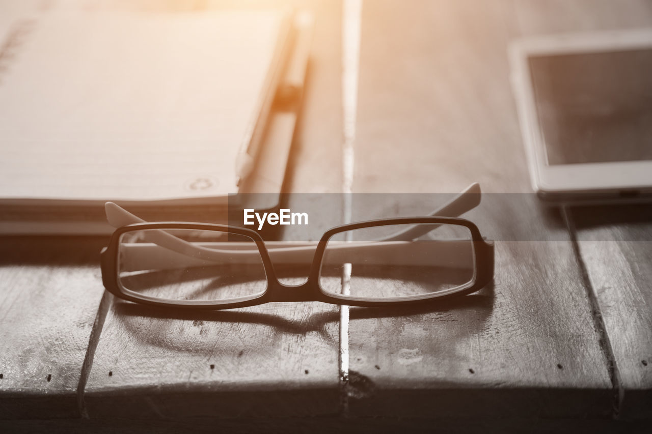 glasses, eyeglasses, table, still life, indoors, close-up, no people, personal accessory, wood - material, focus on foreground, eyewear, transparent, selective focus, eyesight, connection, day, absence, technology