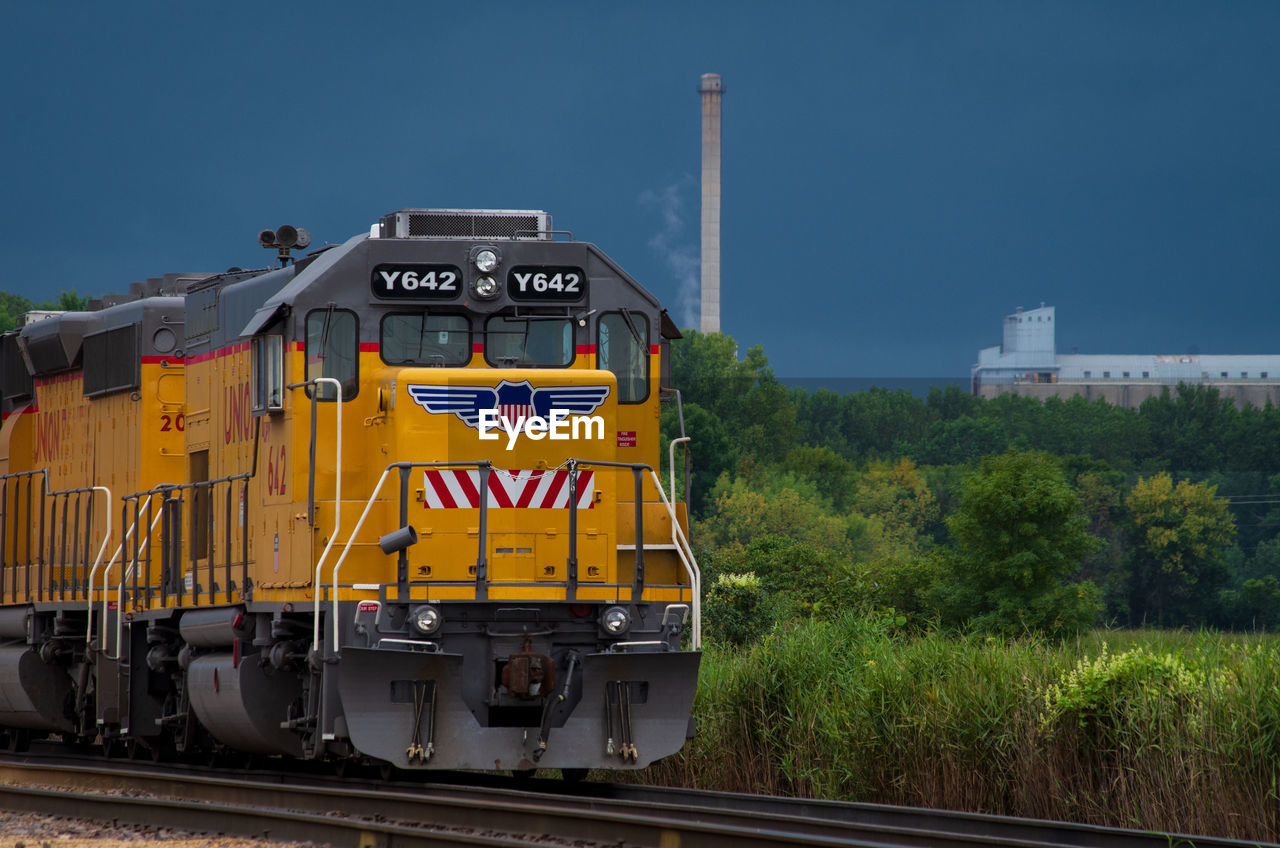 rail transportation, transportation, train, train - vehicle, mode of transportation, railroad track, track, sky, public transportation, no people, nature, plant, day, land vehicle, outdoors, tree, locomotive, yellow, travel, freight train, shunting yard
