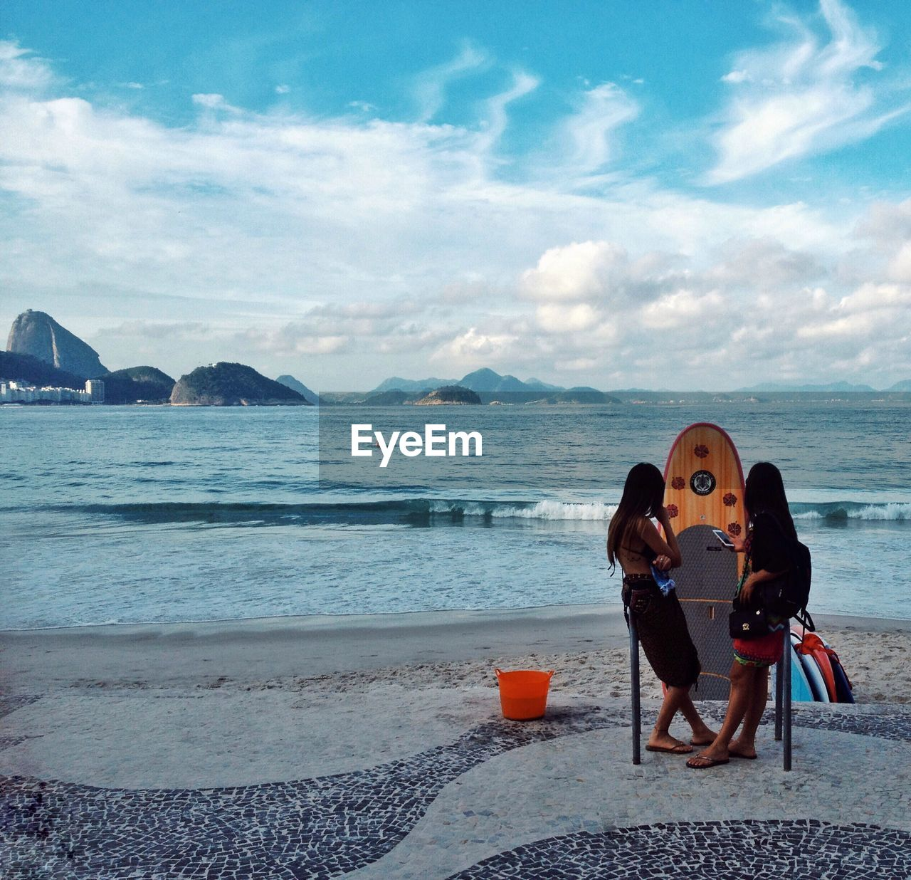 sky, sea, scenics, beach, nature, cloud - sky, mountain, water, real people, vacations, beauty in nature, tranquil scene, two people, full length, outdoors, sand, leisure activity, tranquility, day, young women, women, young adult, people