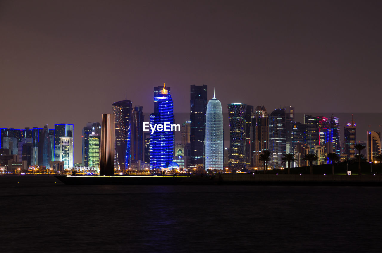 Illuminated Doha Tower And Buildings In City