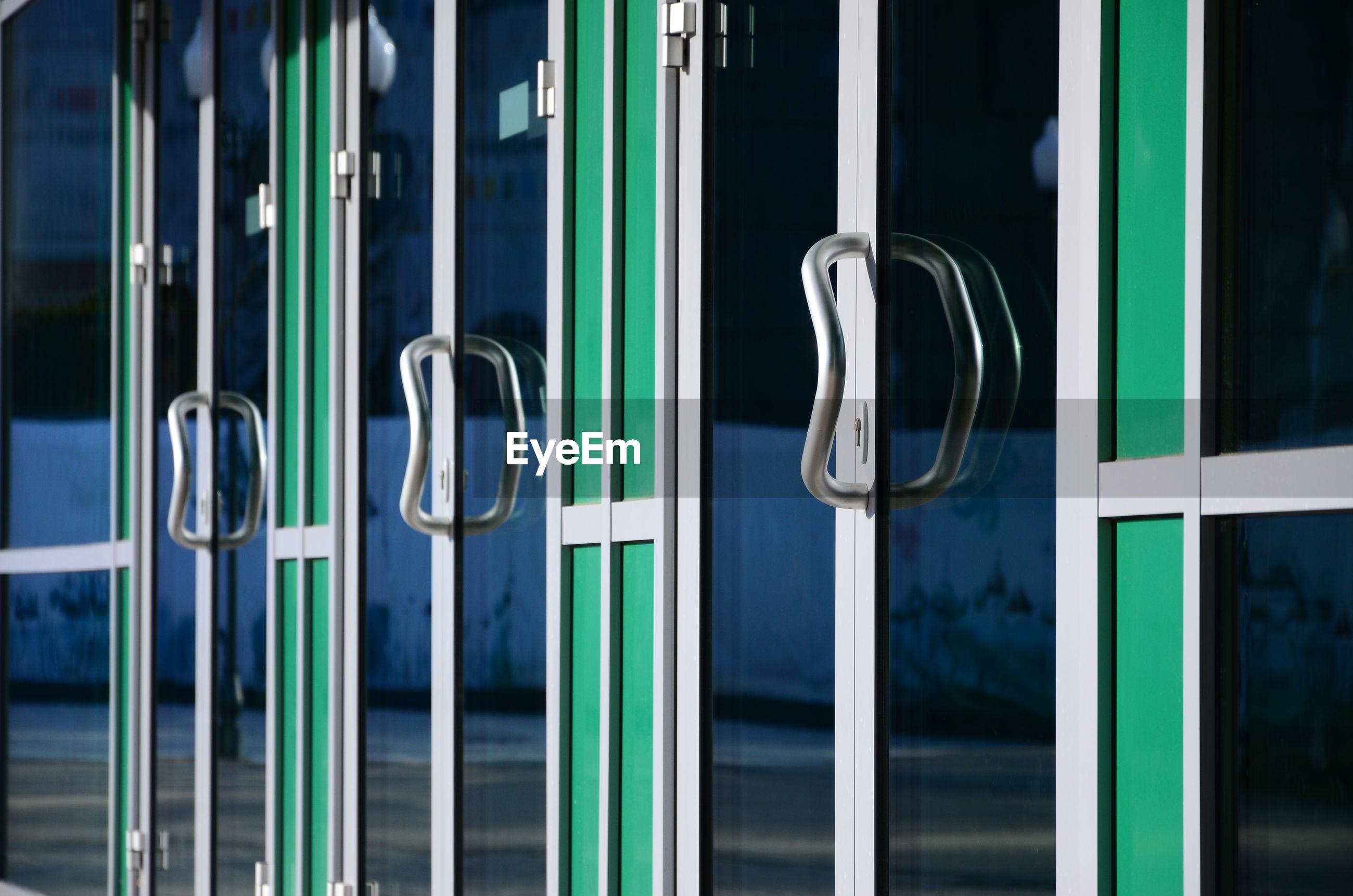Close-up of metal handles hanging from door