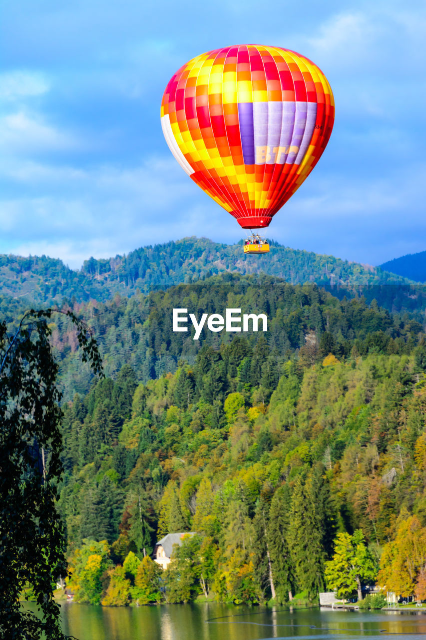 hot air balloon, balloon, air vehicle, transportation, mid-air, adventure, water, flying, sky, nature, mountain, beauty in nature, plant, scenics - nature, mode of transportation, tree, day, non-urban scene, multi colored, ballooning festival, outdoors, no people