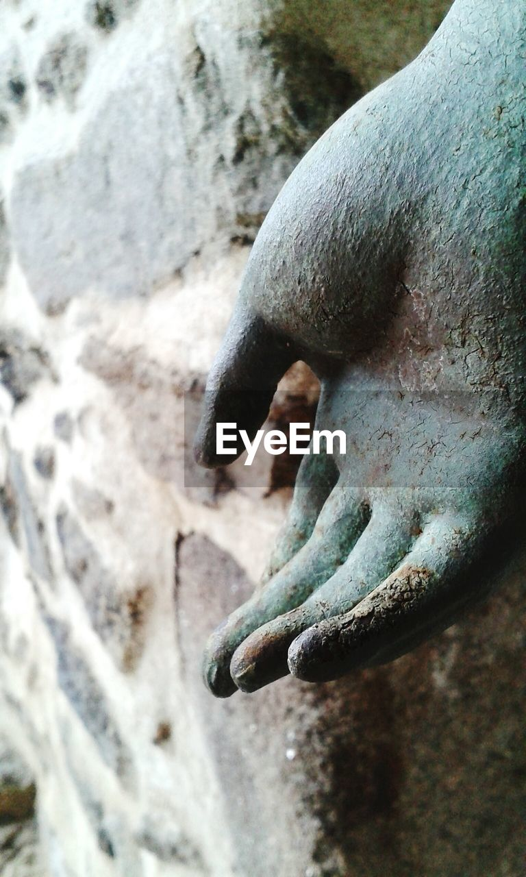 Cropped sculpture hand by stone wall