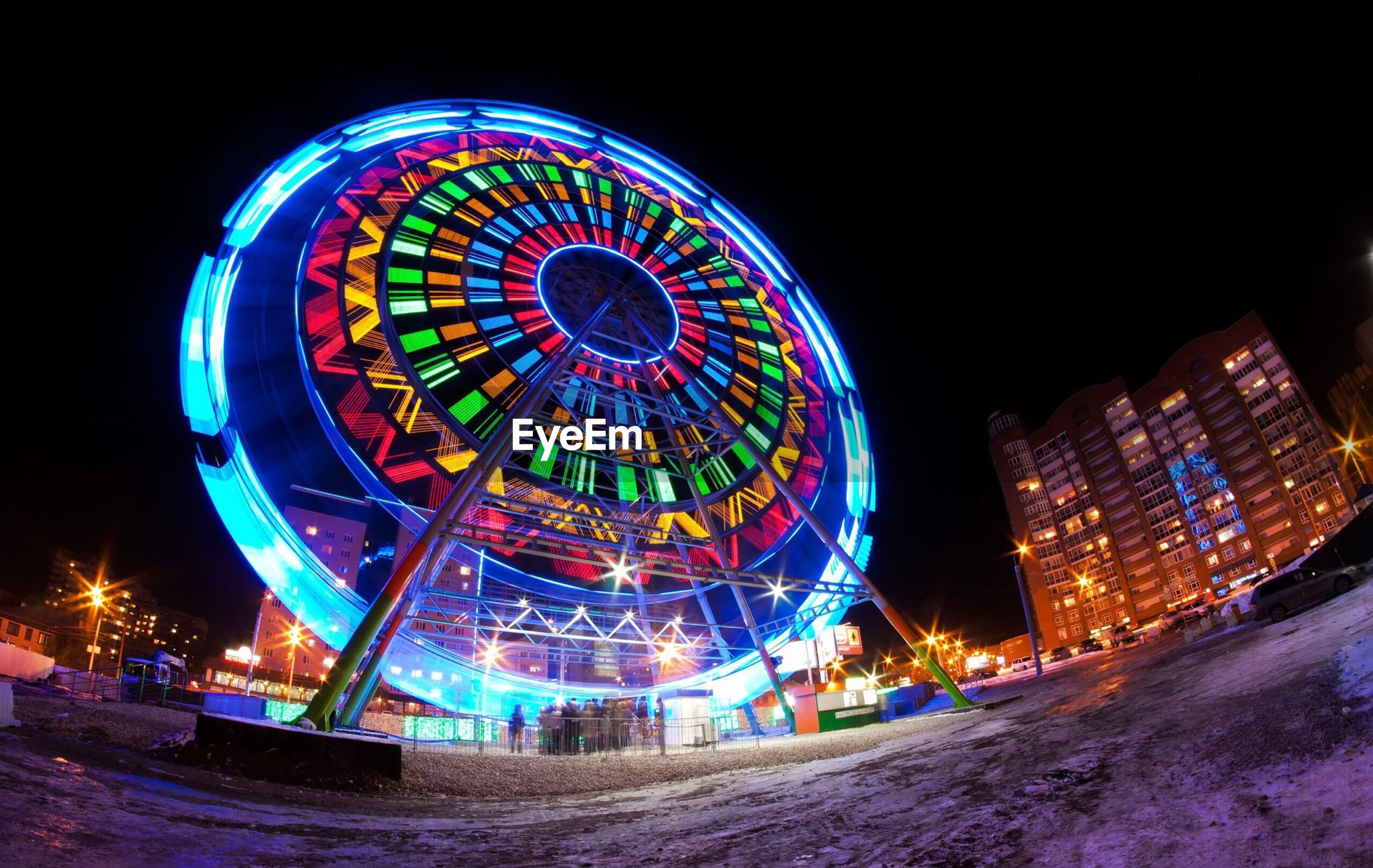 Low angle view of ferris wheel at traveling carnival in city