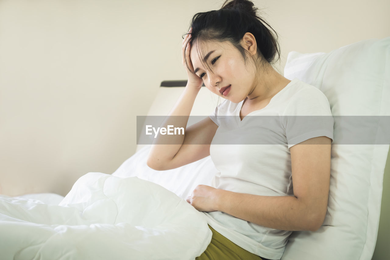 Woman with headache and stomach ache sitting on bed at home