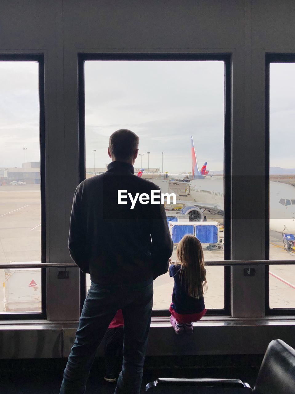 window, rear view, transparent, glass - material, transportation, real people, mode of transportation, men, public transportation, travel, women, looking, air vehicle, people, airplane, airport, standing, lifestyles, looking through window, three quarter length, outdoors