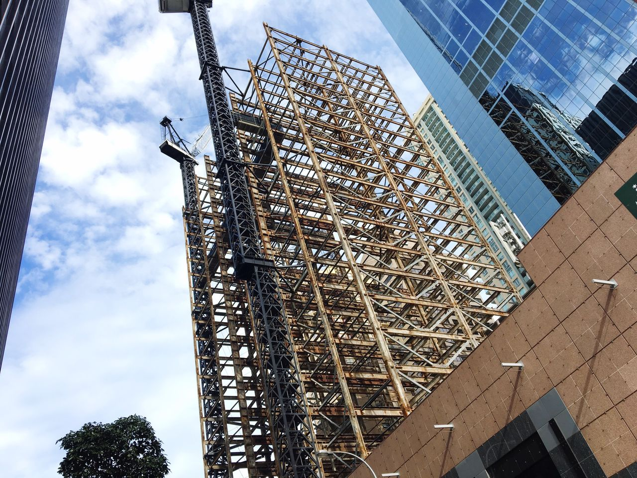 architecture, built structure, low angle view, construction site, sky, development, building exterior, cloud - sky, building - activity, day, construction frame, outdoors, no people, skyscraper, tree
