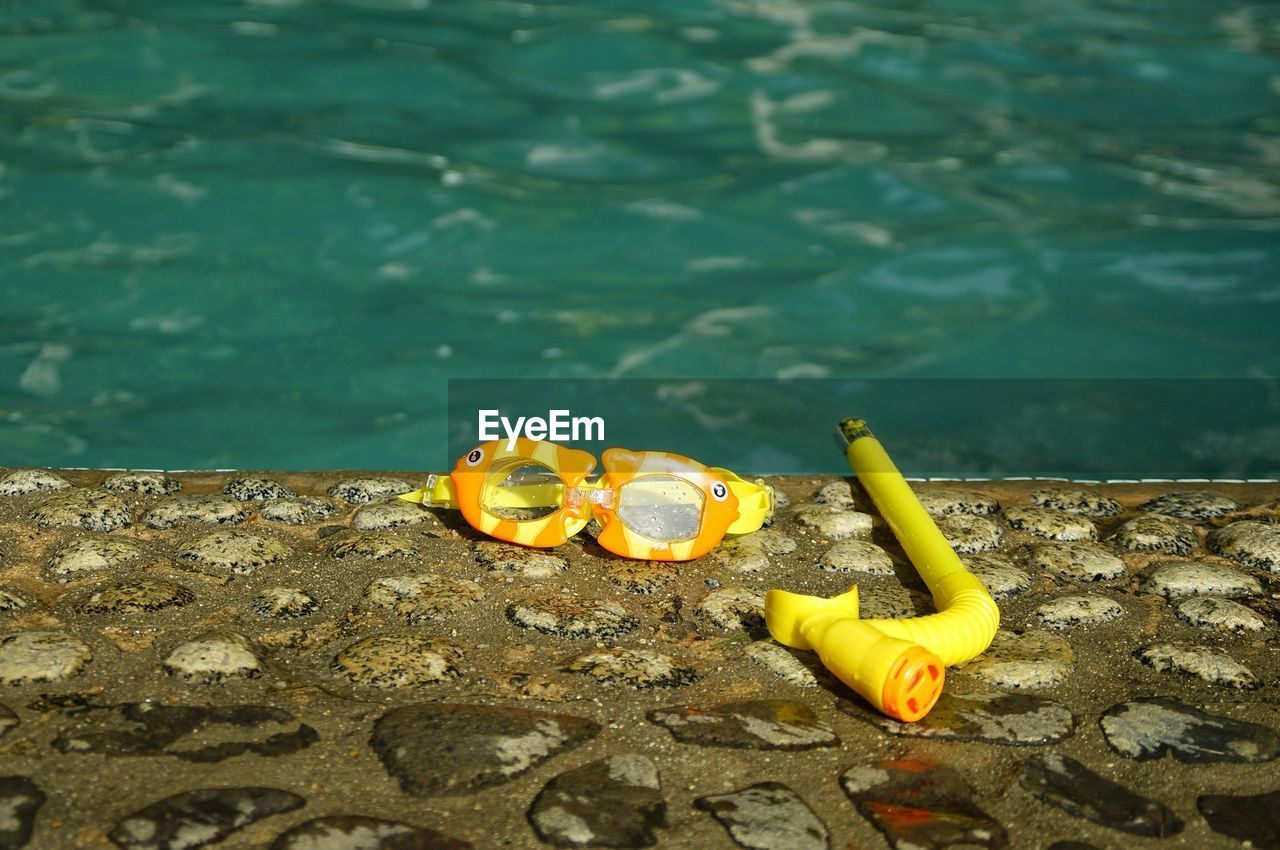 HIGH ANGLE VIEW OF YELLOW TOY IN LAKE
