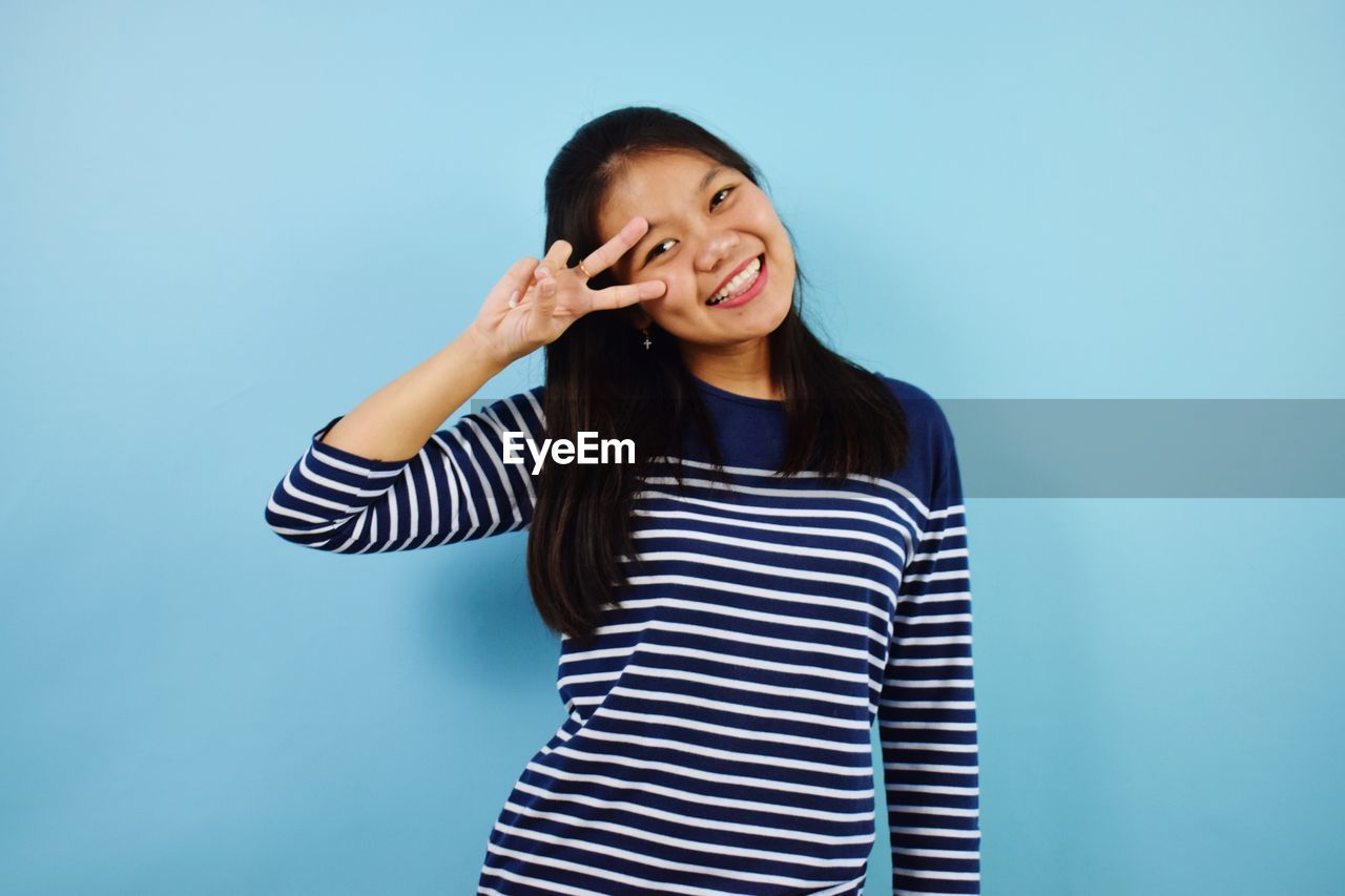 HAPPY YOUNG WOMAN AGAINST BLUE BACKGROUND