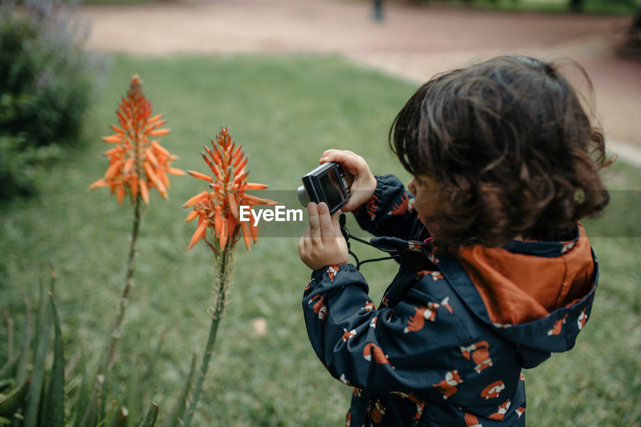 Cute girl photographing plant outdoors