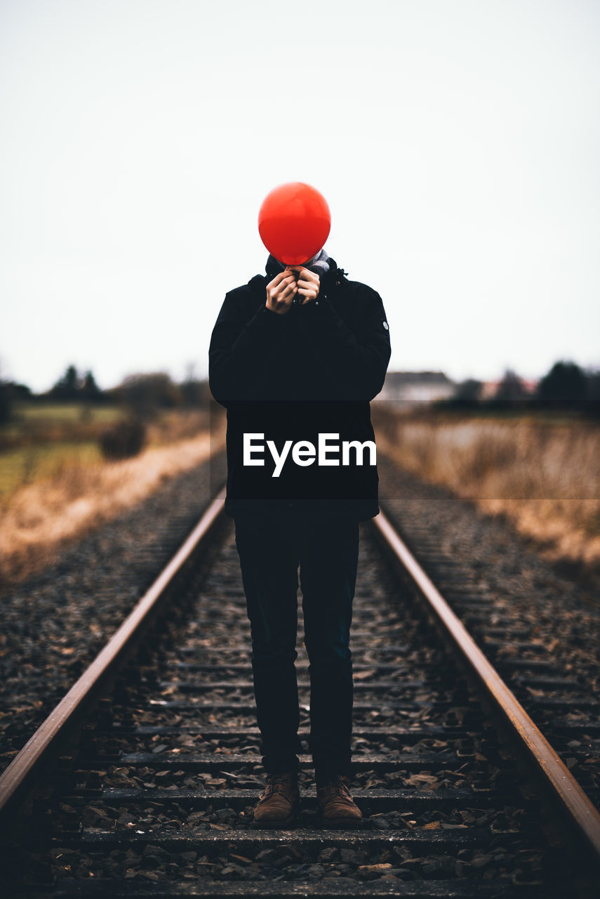 Man Covering Face With Red Balloon While Standing On Railroad Track Against Sky