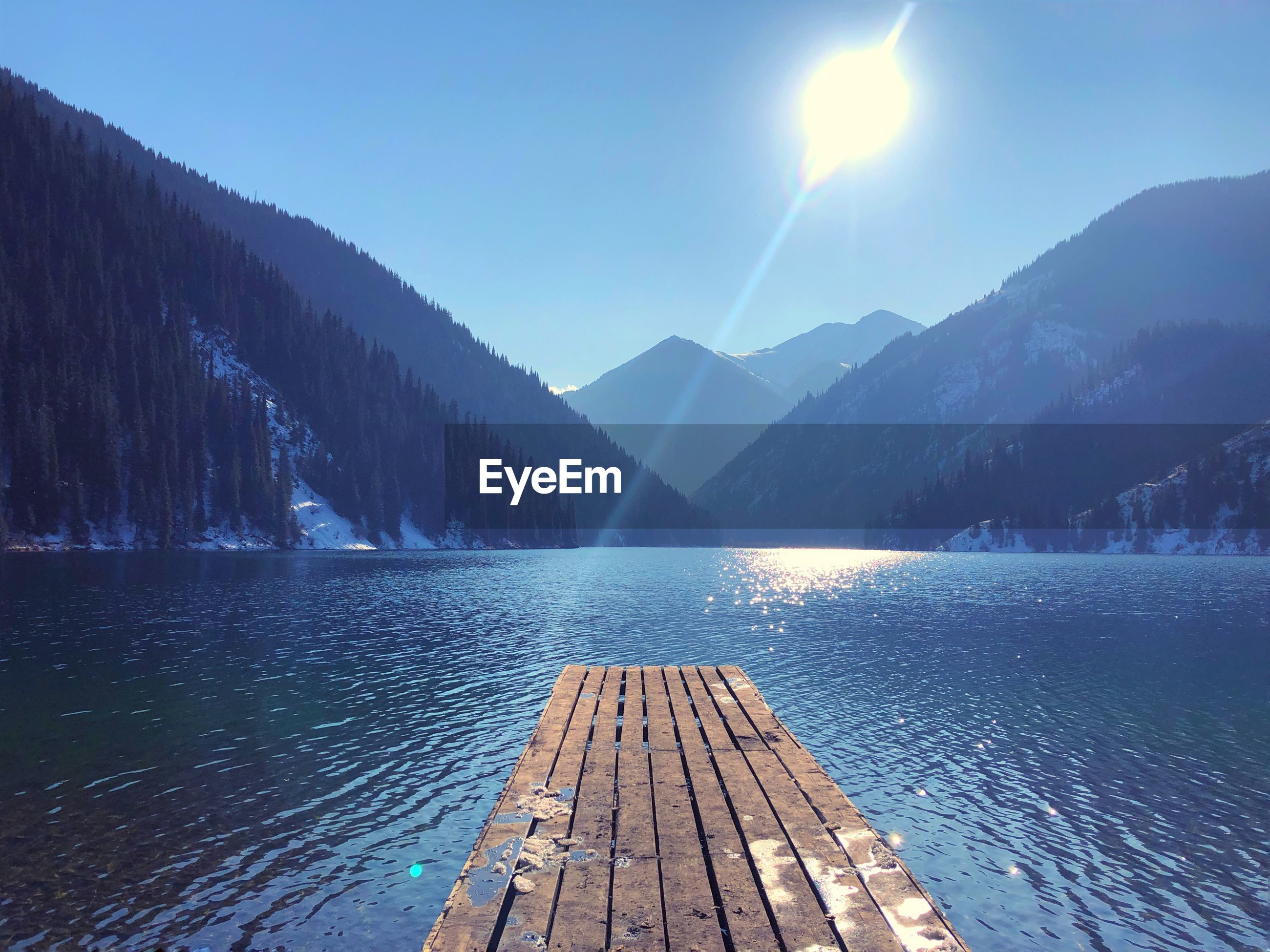 Scenic view of lake by mountains against bright sun