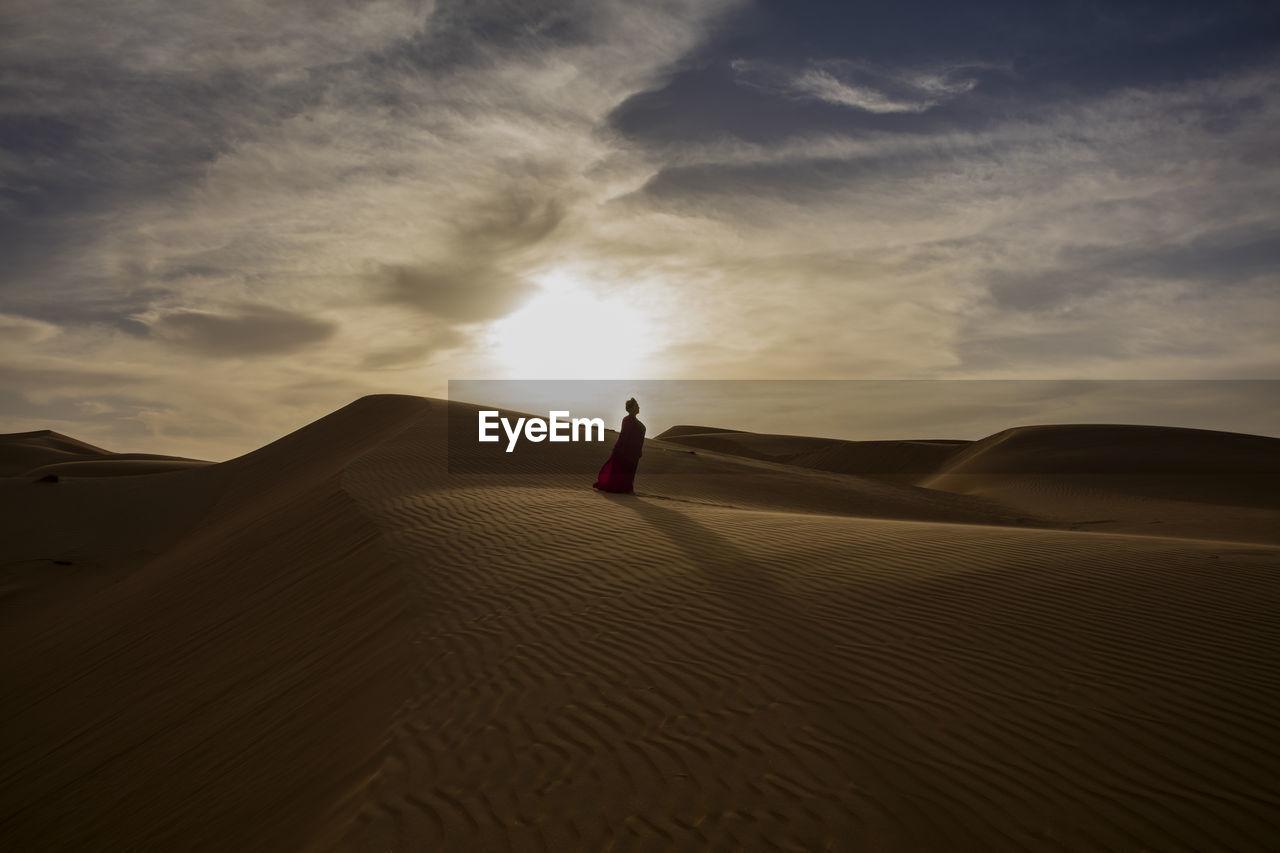 Woman standing on sand dune at desert against sky