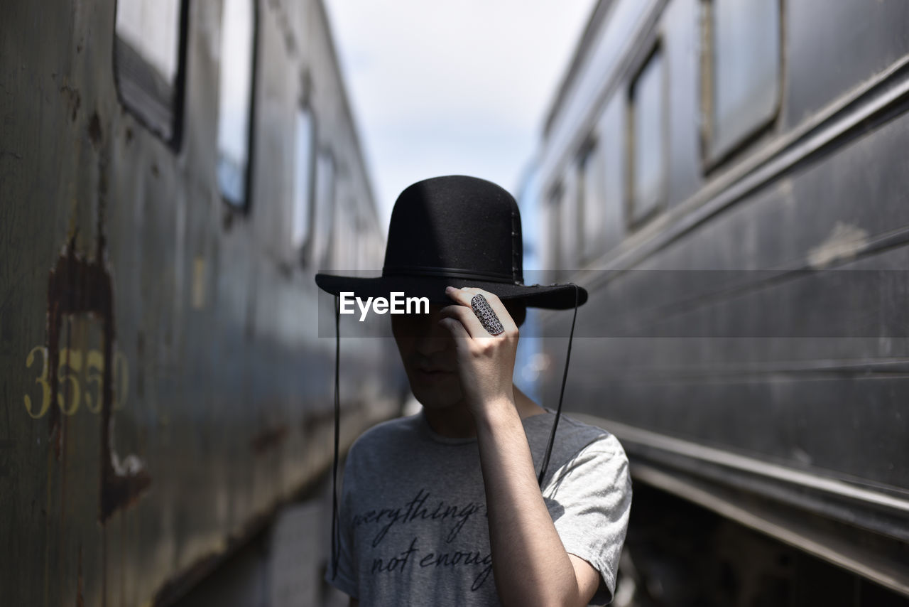 Man wearing hat against trains
