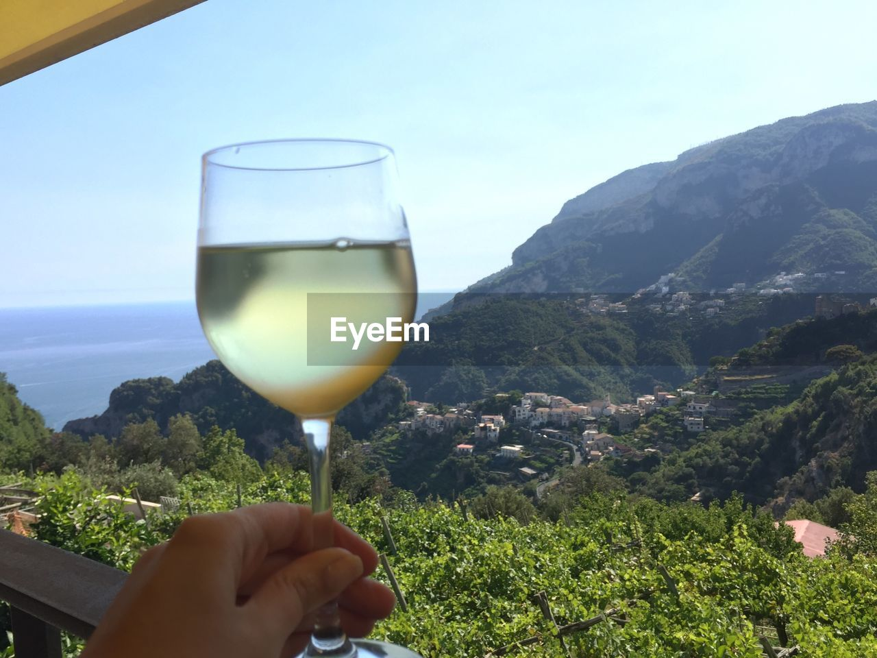human hand, hand, drink, food and drink, human body part, real people, alcohol, glass, one person, holding, refreshment, mountain, lifestyles, wine, nature, freshness, wineglass, sky, finger, human finger, body part, mountain range, outdoors