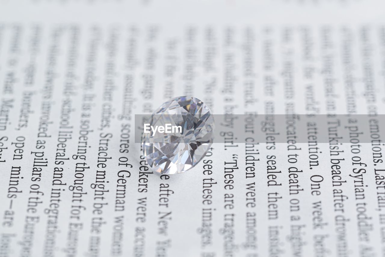 diamond - gemstone, jewelry, ring, text, wealth, wedding, event, emotion, wedding ring, love, close-up, indoors, no people, single object, positive emotion, western script, selective focus, engagement ring, communication, studio shot, luxury, expense
