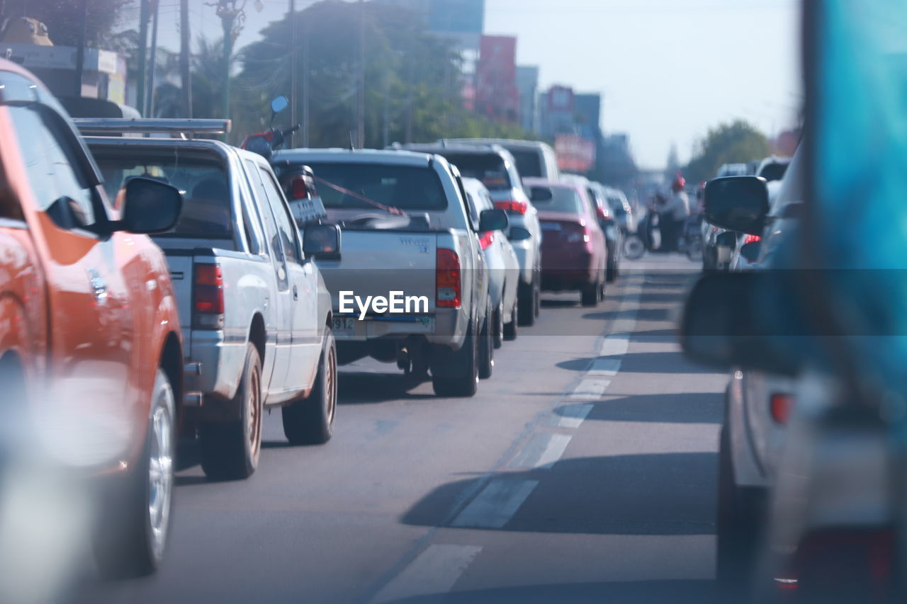 motor vehicle, transportation, mode of transportation, car, city, land vehicle, street, road, in a row, day, architecture, traffic, selective focus, incidental people, sign, city street, outdoors, city life, traffic jam, travel, government