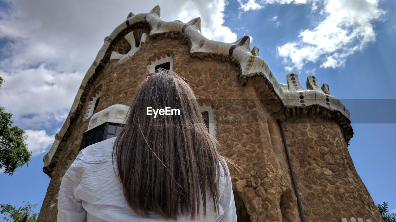 low angle view, architecture, built structure, sky, cloud - sky, building exterior, rear view, day, history, religion, one person, outdoors, spirituality, real people, ancient, leisure activity, place of worship, travel destinations, old ruin, ancient civilization, tree, women