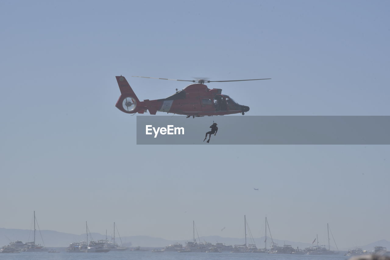 sky, mode of transportation, water, transportation, clear sky, flying, mid-air, nature, nautical vessel, air vehicle, sea, day, helicopter, waterfront, copy space, airplane, military, outdoors, motion, no people, government, plane, aerospace industry, sailboat