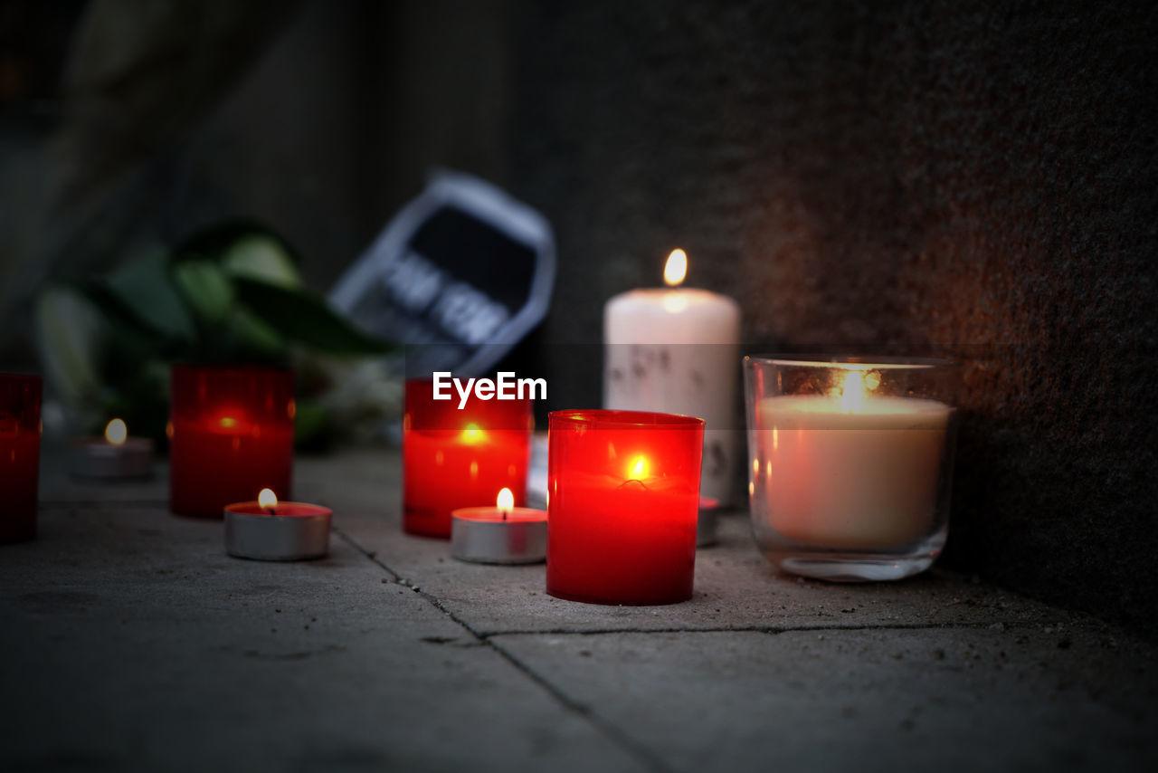 Tea Light Candles On Floor Against Wall