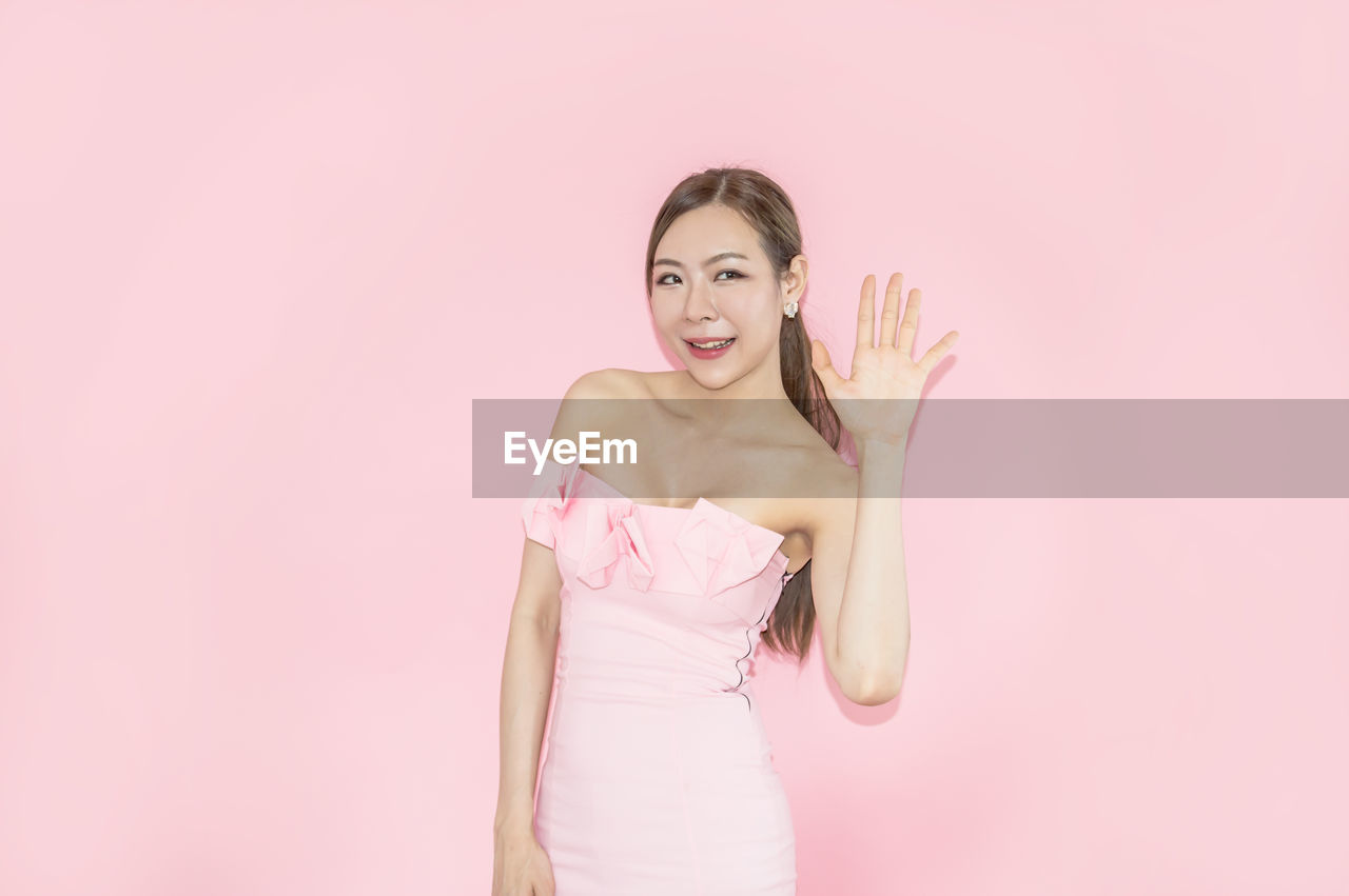 Woman Gesturing While Standing Against Pink Background
