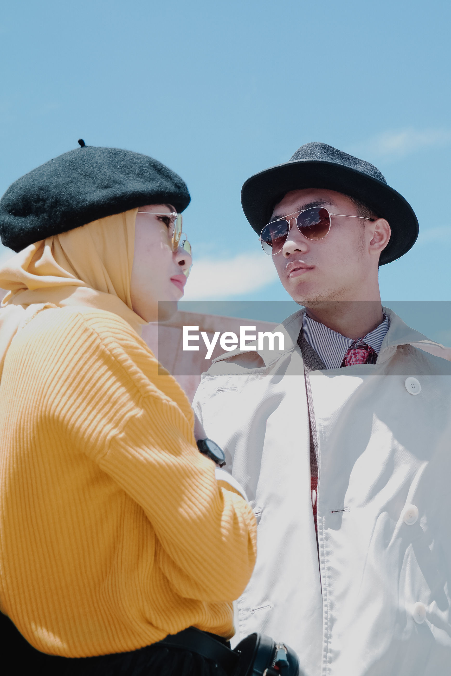 Fashionable couple wearing hats and warm clothing in city
