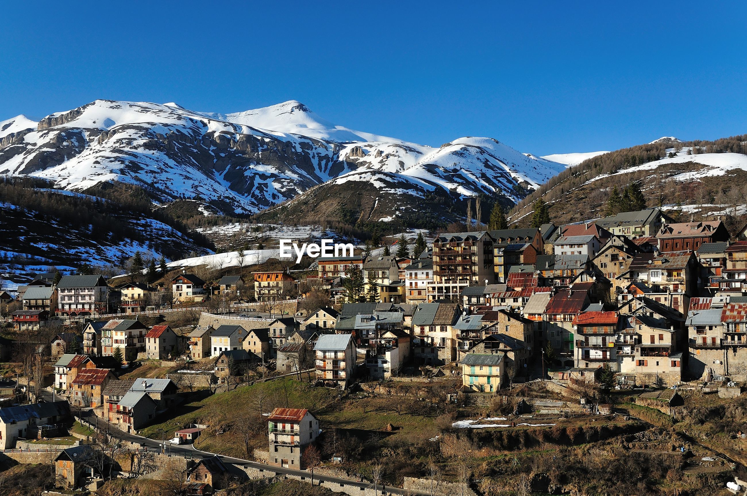 Aerial view of townscape by mountain against clear sky