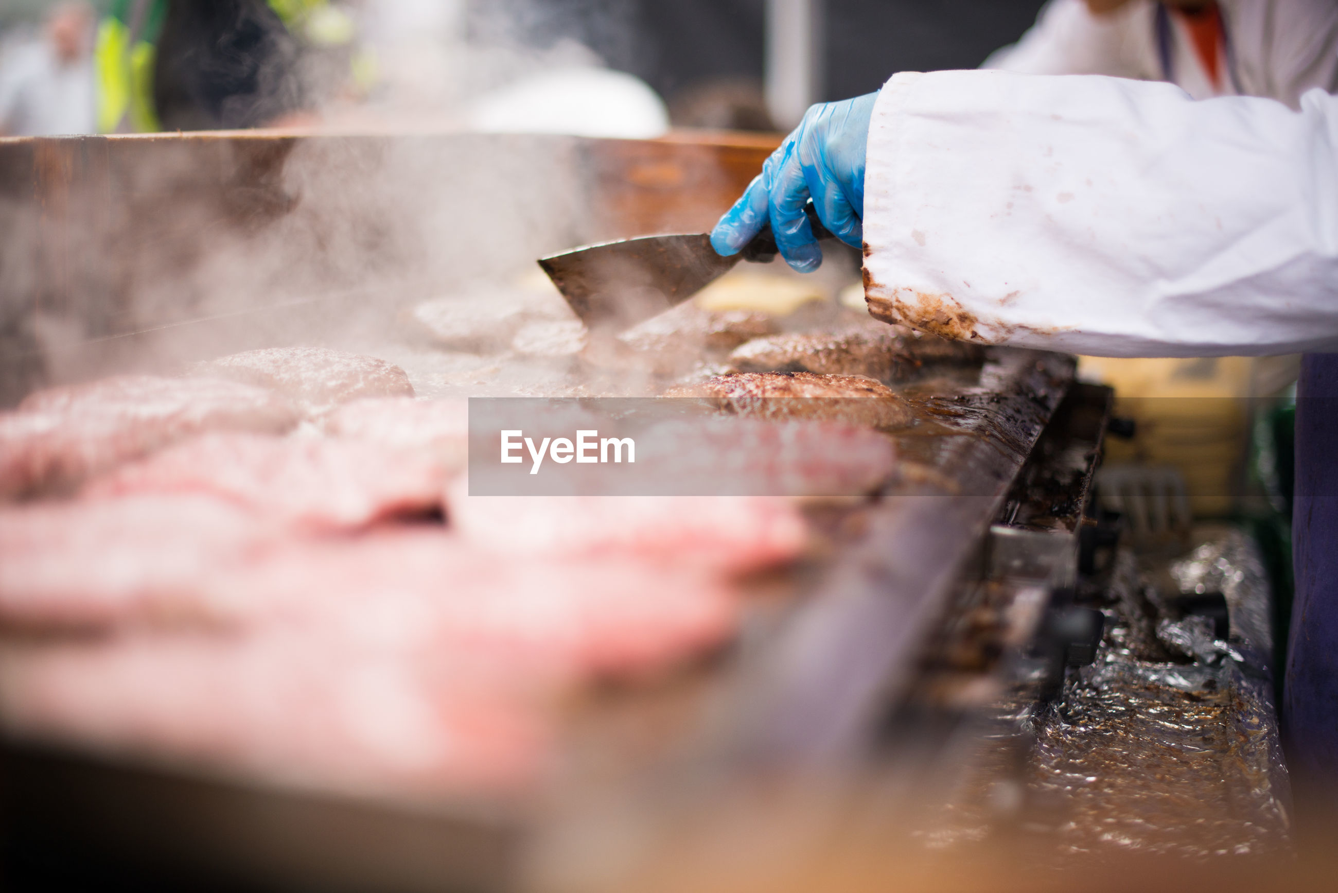 Midsection of person preparing burger at street market