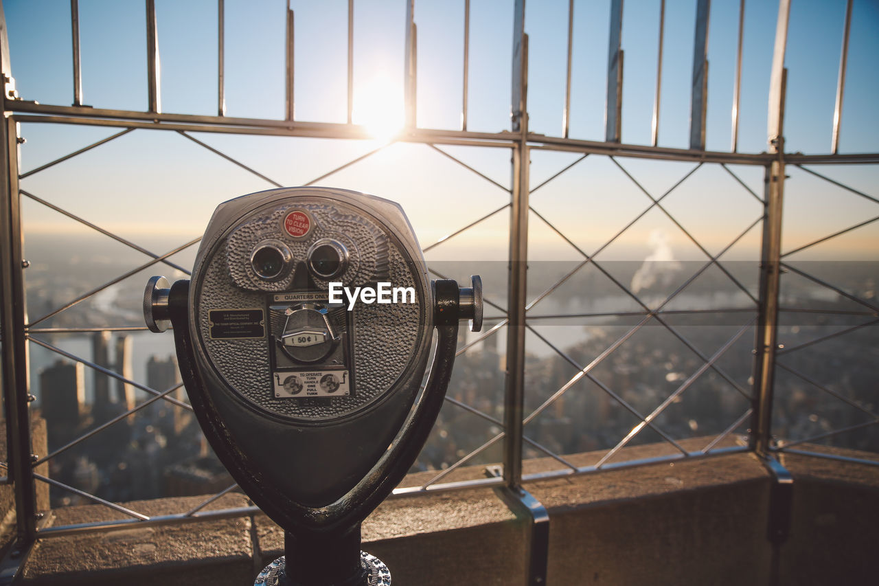 coin-operated binoculars, metal, railing, outdoors, no people, bridge - man made structure, cityscape, sky, day, built structure, city, close-up, architecture, water