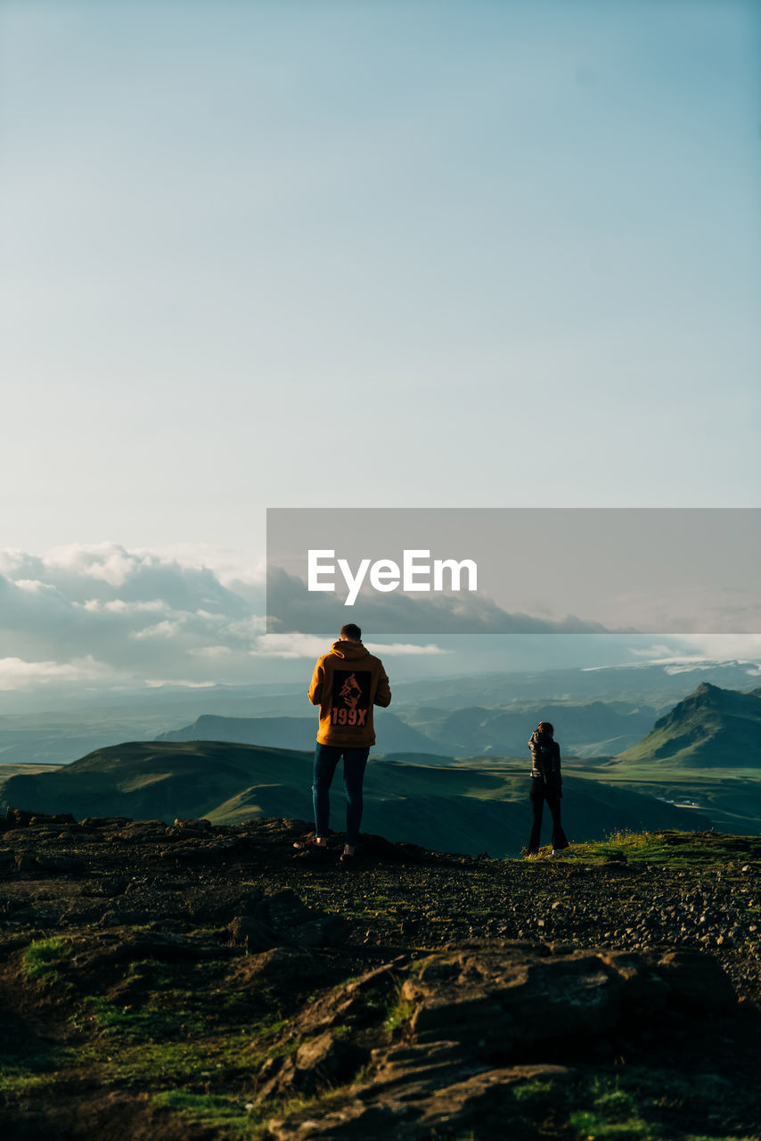 sky, real people, beauty in nature, standing, leisure activity, scenics - nature, two people, full length, mountain, nature, lifestyles, cloud - sky, adult, tranquility, tranquil scene, men, women, rear view, people, idyllic, outdoors, couple - relationship