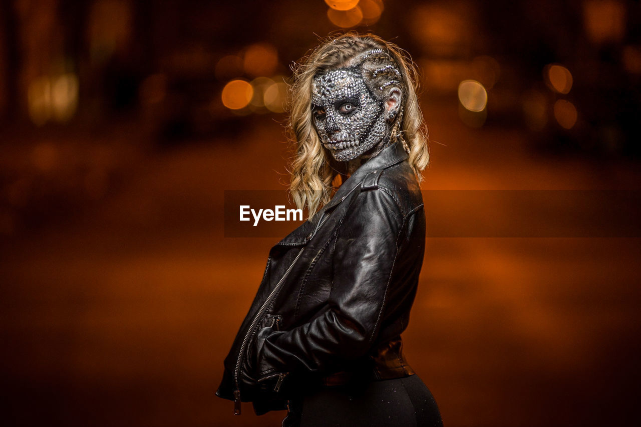 Portrait Of Woman Wearing Spooky Mask While Standing On Street At Night
