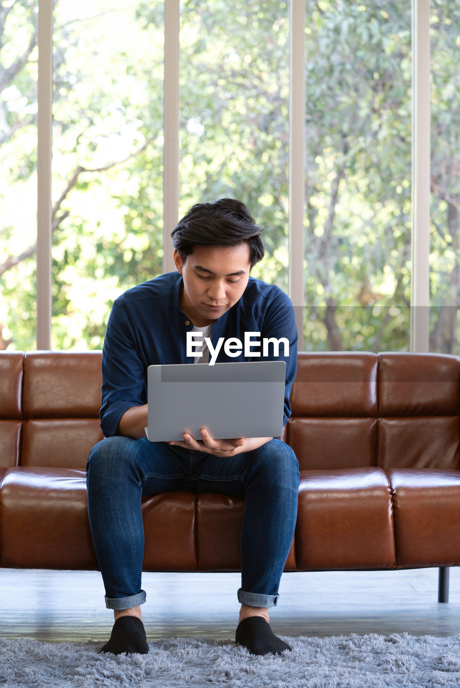 Young man using laptop while sitting on sofa