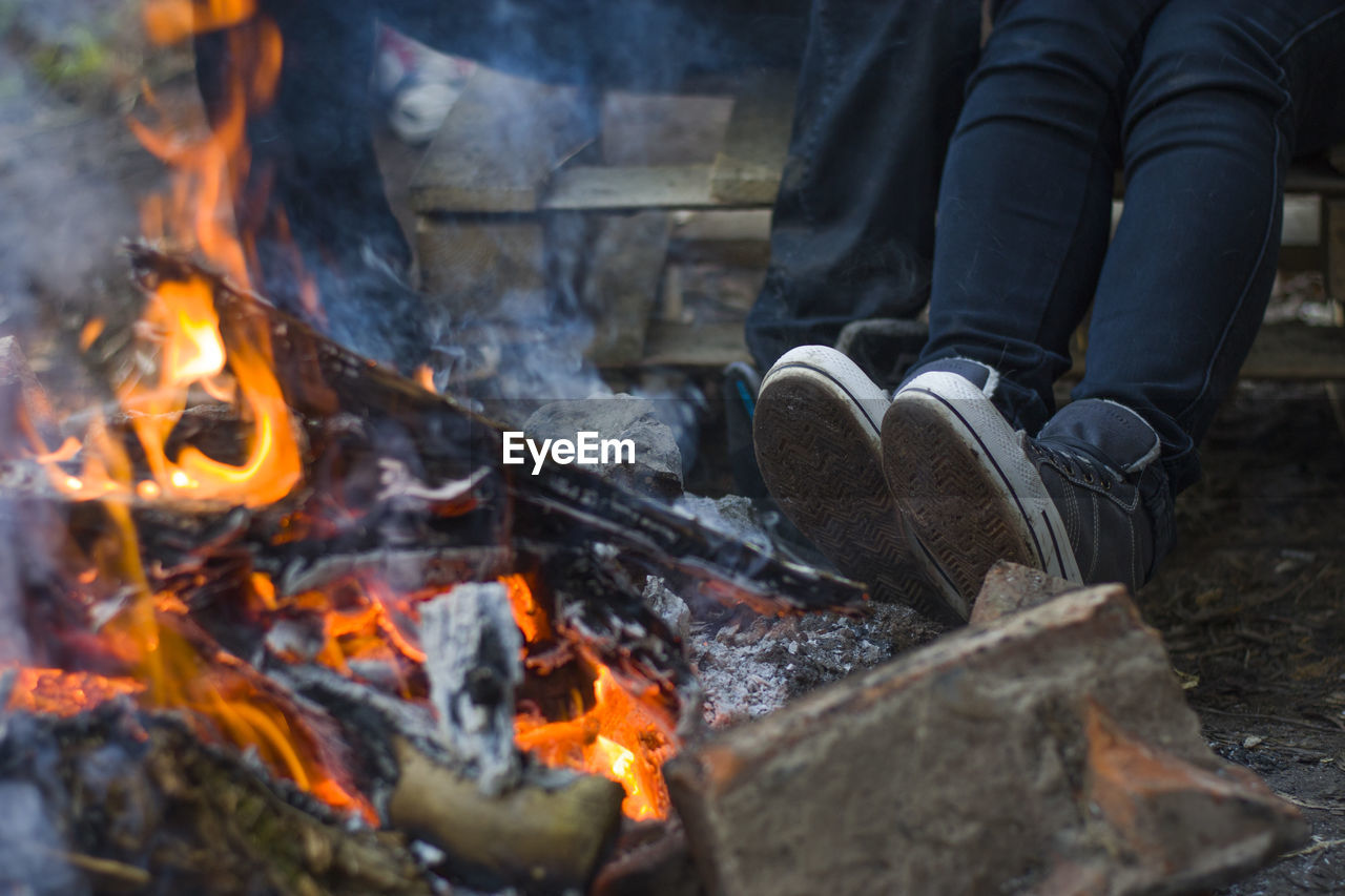 Low Section Of People Sitting Near Bonfire