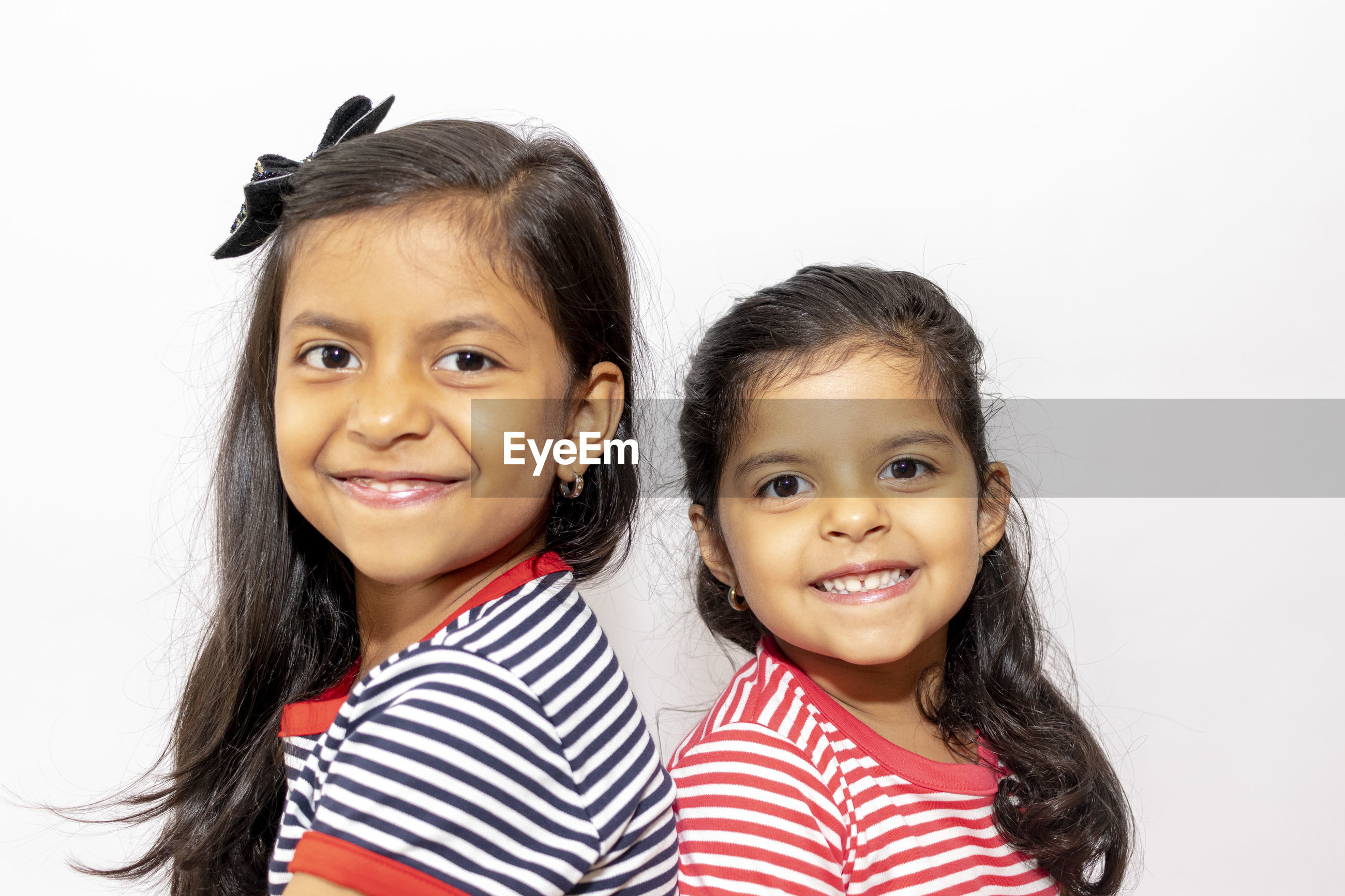 Portrait of smiling siblings against white background