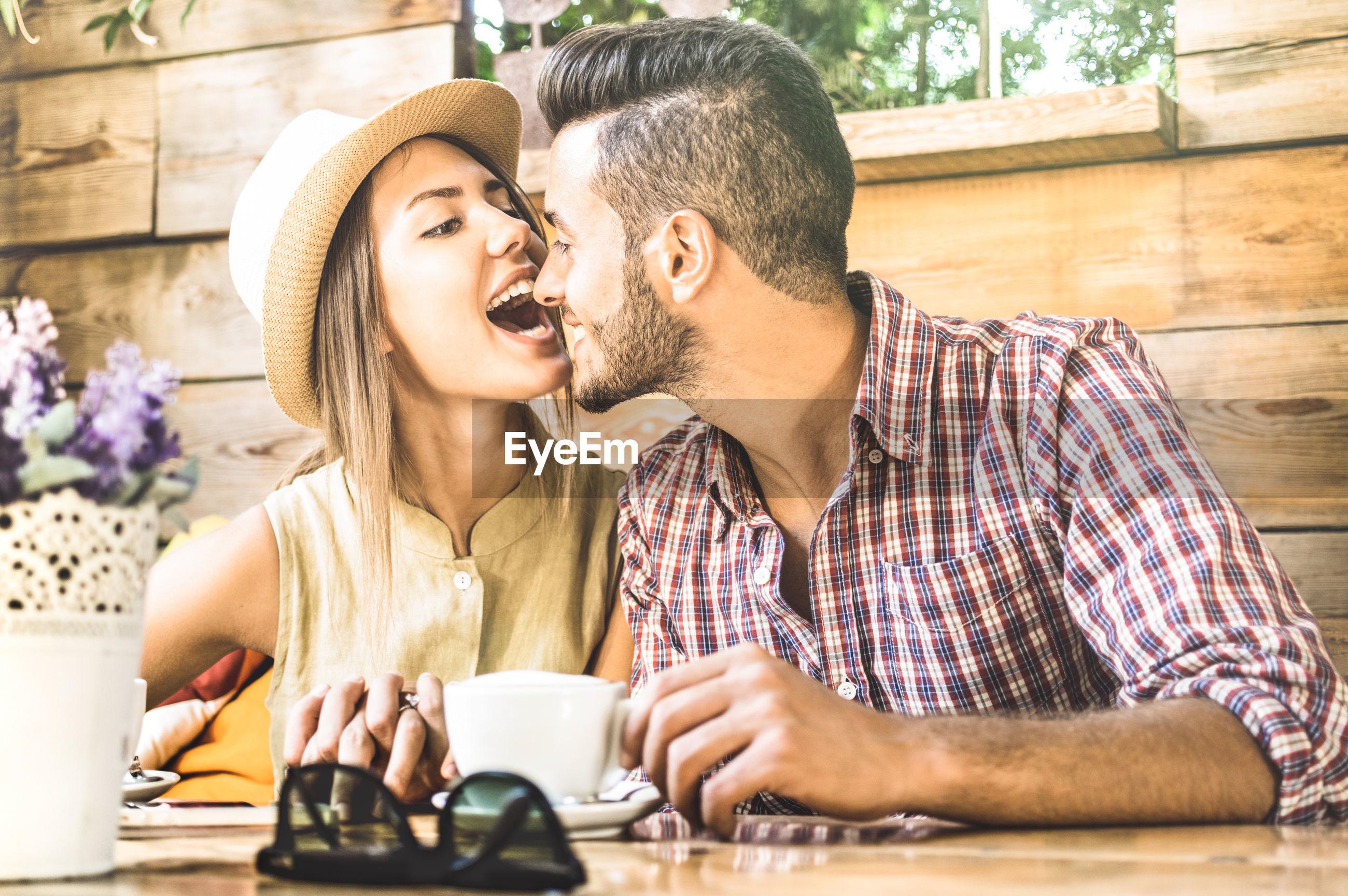 Romantic tourist couple spending leisure time at outdoor restaurant