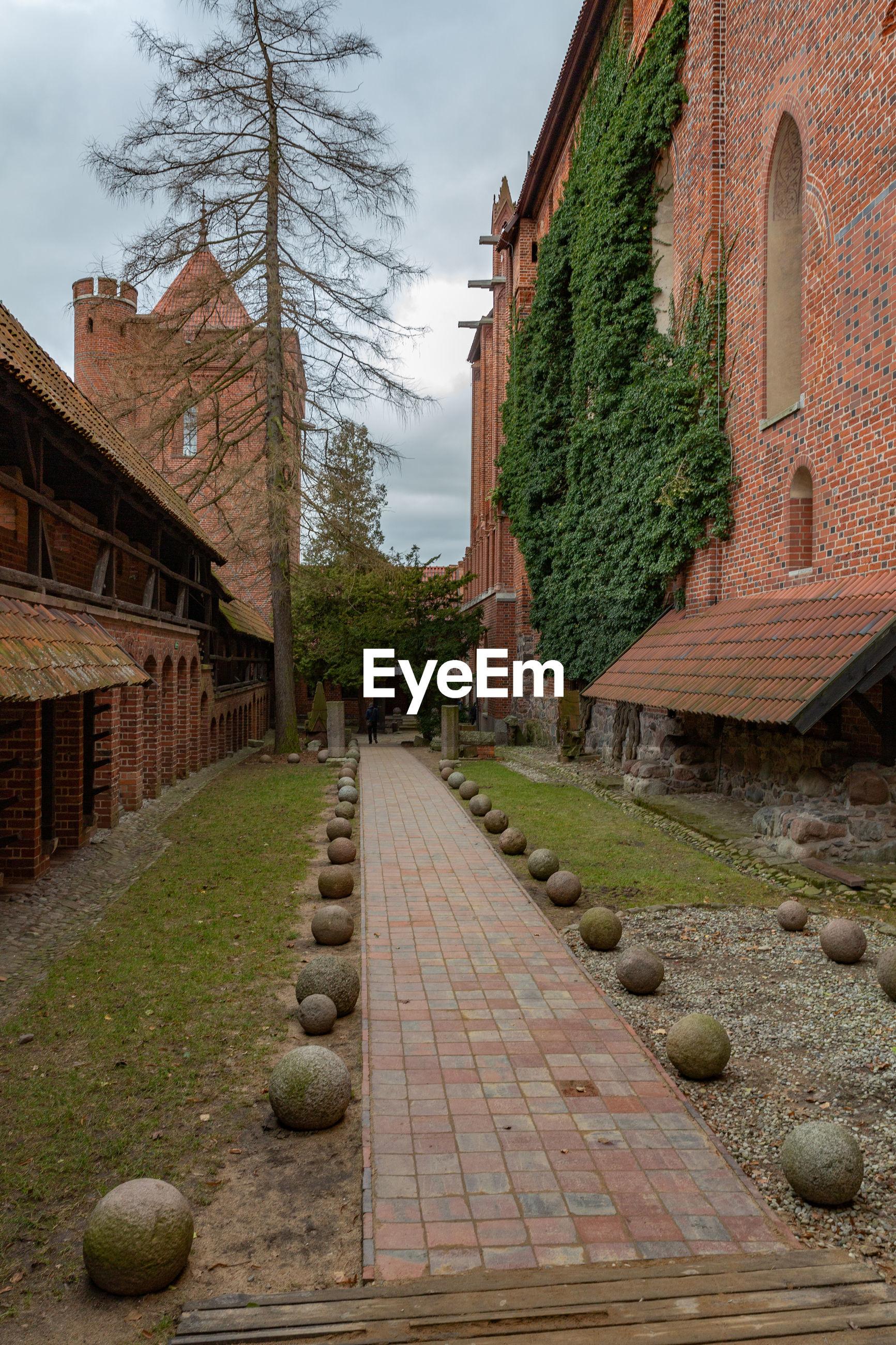 Footpath amidst buildings against sky, malbork castle.