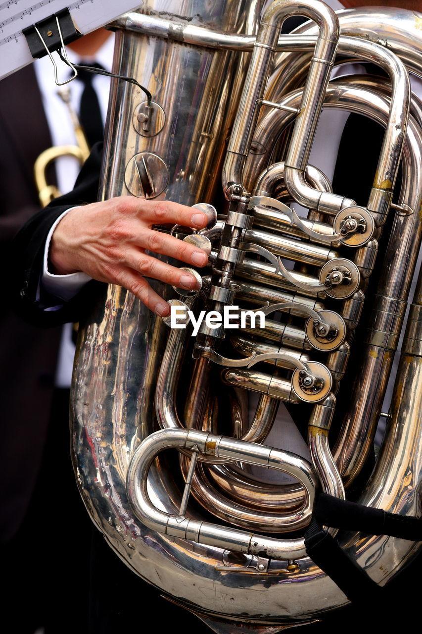 Midsection of man playing tuba