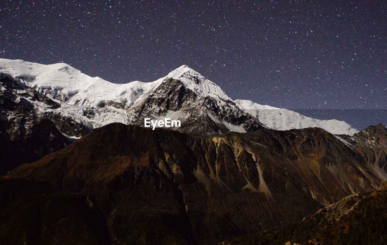 mountain, scenics - nature, beauty in nature, sky, snow, mountain range, space, environment, astronomy, night, landscape, star - space, cold temperature, no people, snowcapped mountain, nature, tranquil scene, tranquility, mountain peak, outdoors, formation