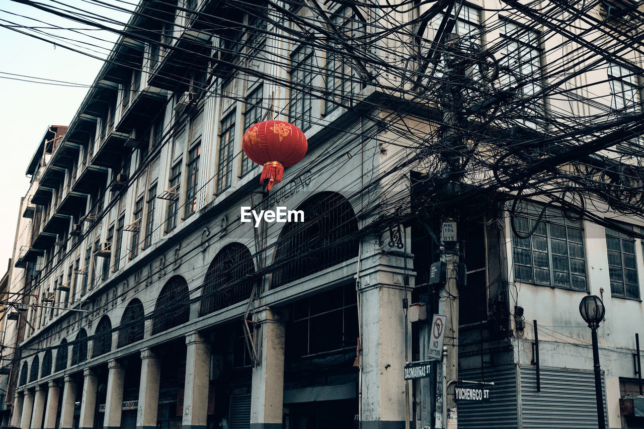 LOW ANGLE VIEW OF RED LANTERNS HANGING ON STREET BY BUILDINGS