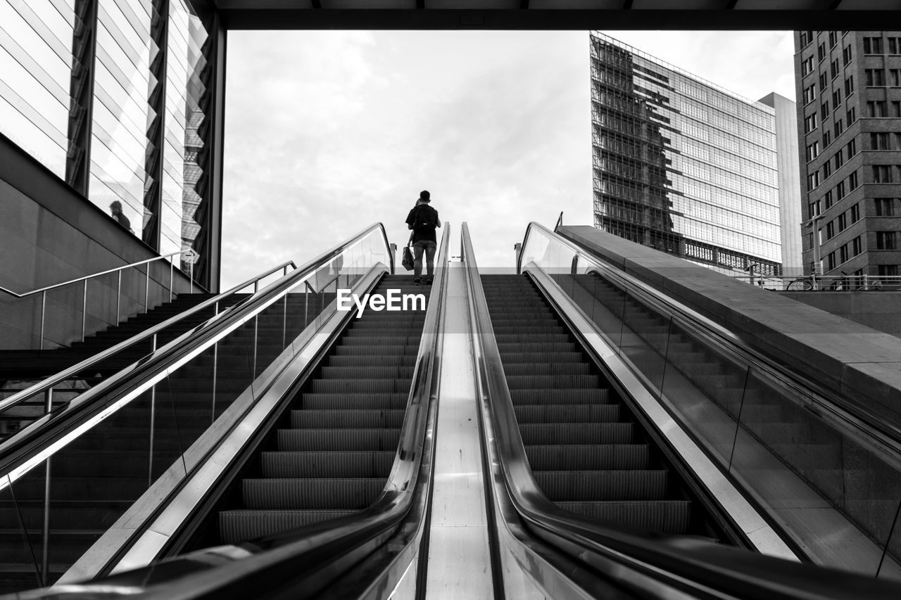 Low Angle View Of Man Standing On Escalator Against Cloudy Sky