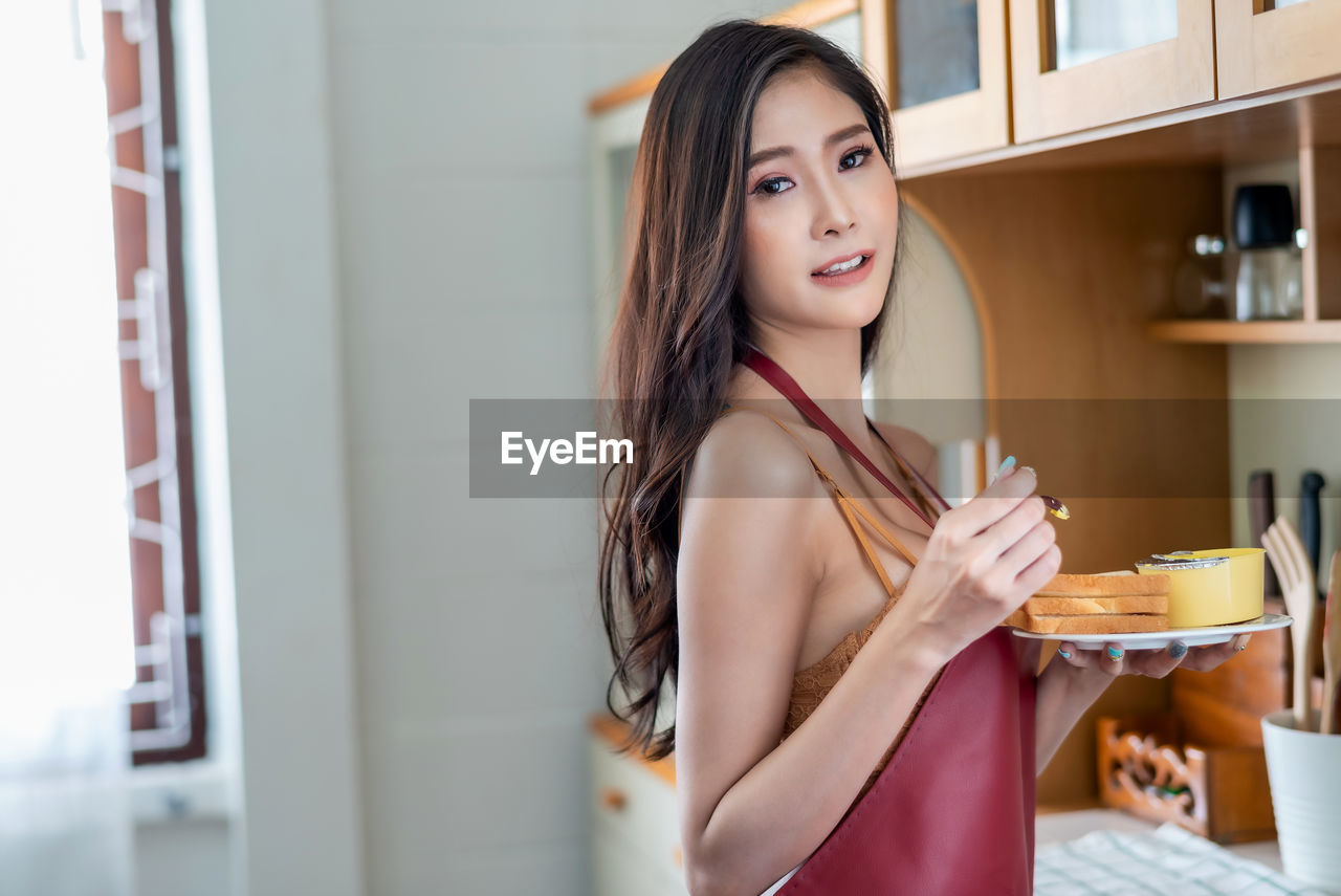 one person, young women, young adult, real people, indoors, standing, lifestyles, beauty, smiling, beautiful woman, hairstyle, home interior, portrait, leisure activity, women, food and drink, adult, long hair, looking at camera, hair