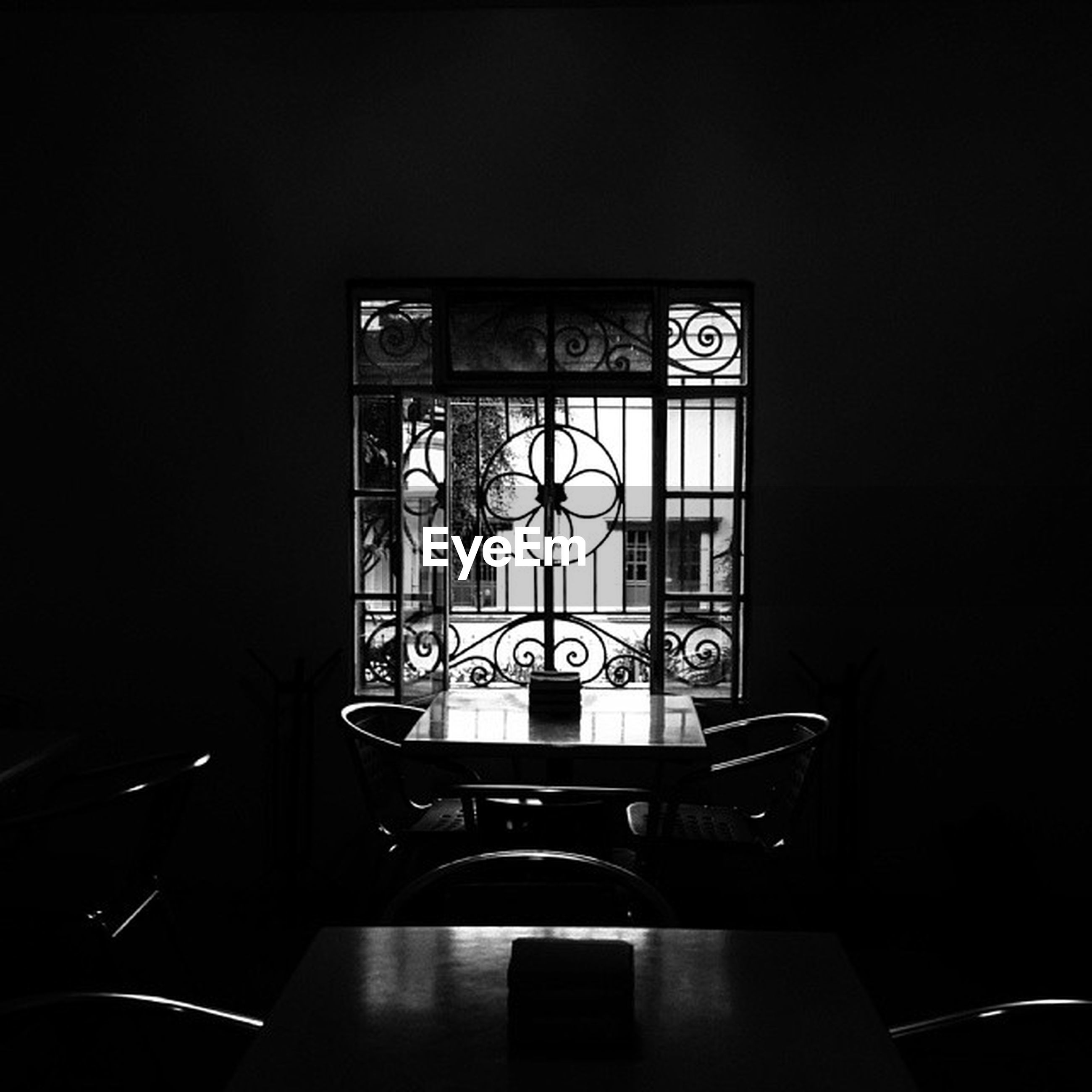 indoors, communication, window, text, western script, architecture, built structure, no people, glass - material, table, absence, copy space, illuminated, dark, empty, reflection, technology, clock, wall - building feature, day