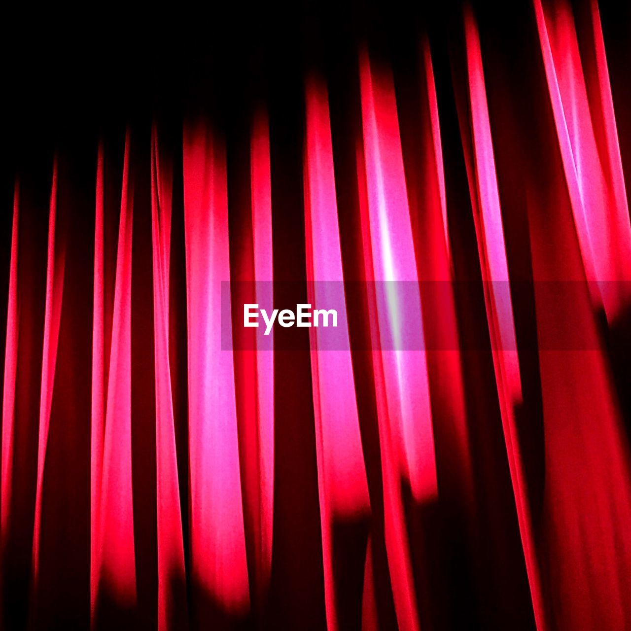 indoors, red, no people, close-up, pattern, lighting equipment, illuminated, night, backgrounds, full frame, light, arts culture and entertainment, curtain, light - natural phenomenon, abstract, music, side by side, motion, electricity, glowing, nightlife, black background, stage