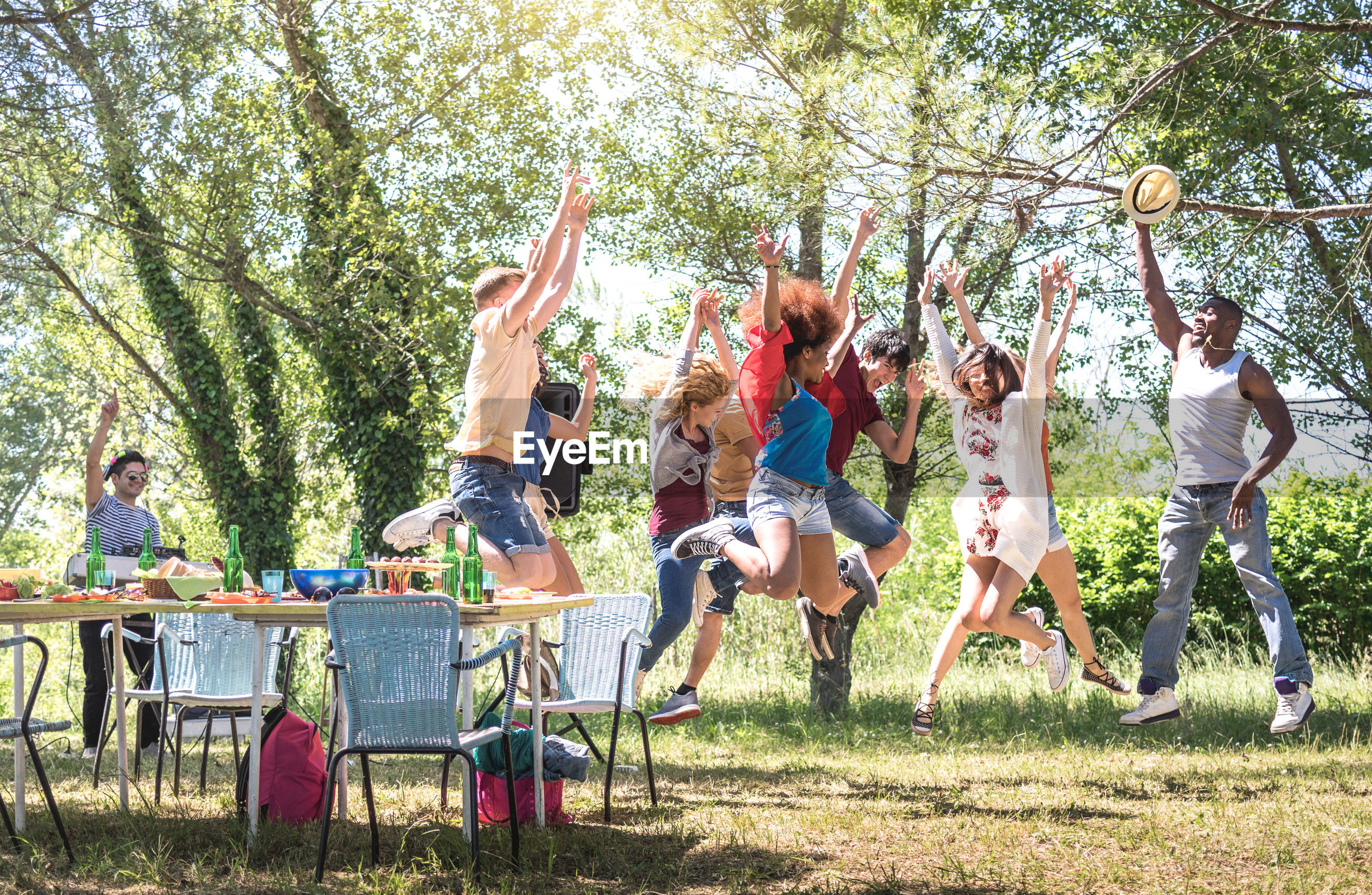 Cheerful friends jumping with arms raised